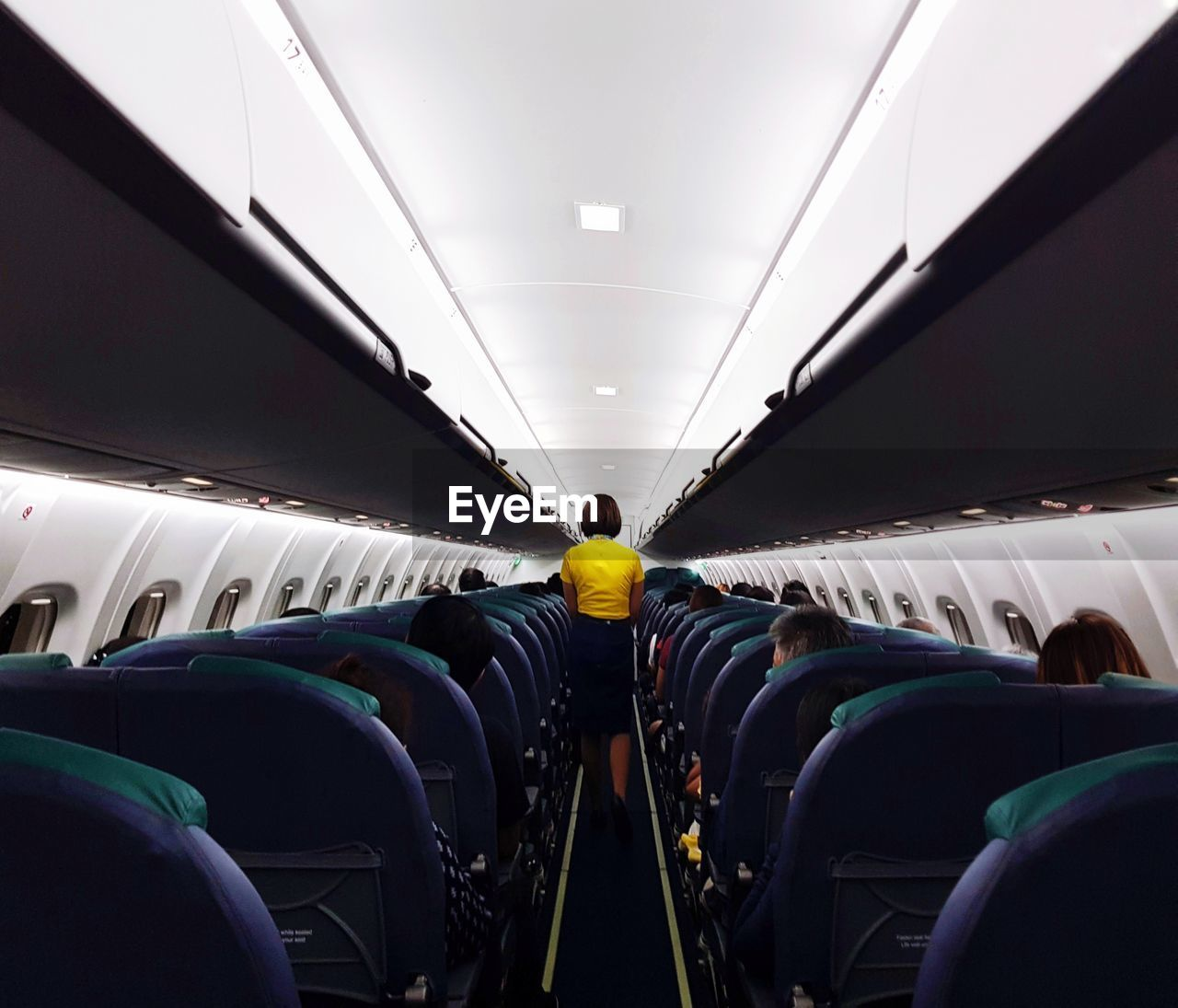 Rear view of air stewardess standing amidst passengers on seats in airplane