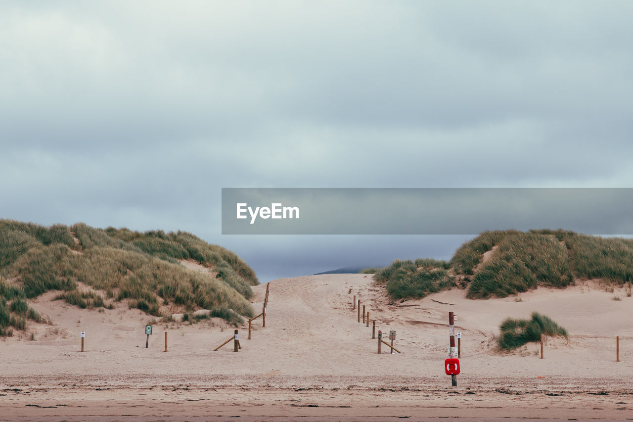 land, cloud - sky, sky, beach, sand, scenics - nature, tranquil scene, nature, tranquility, beauty in nature, day, incidental people, sea, tree, environment, water, plant, outdoors, non-urban scene, landscape