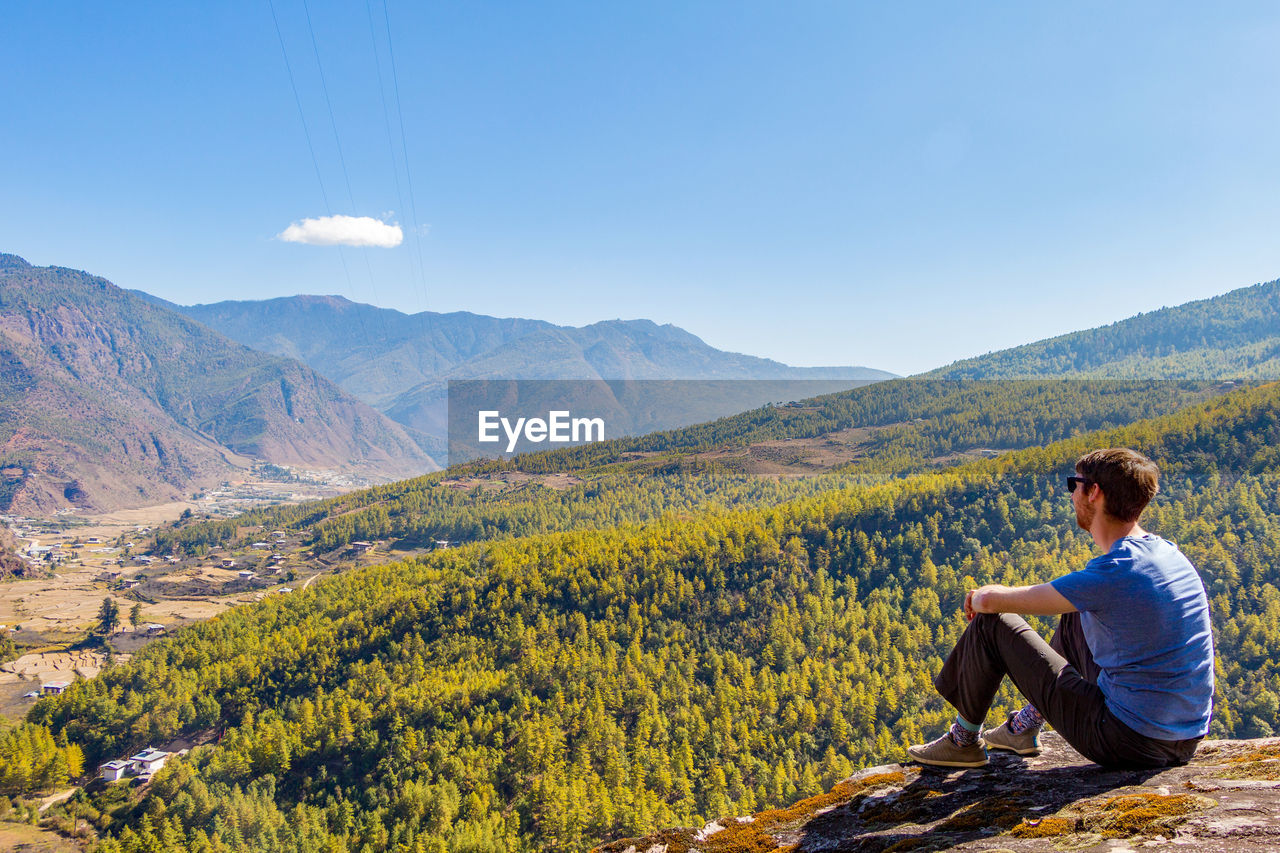 Mid Adult Man Looking At Mountains While Sitting On Cliff Against Sky