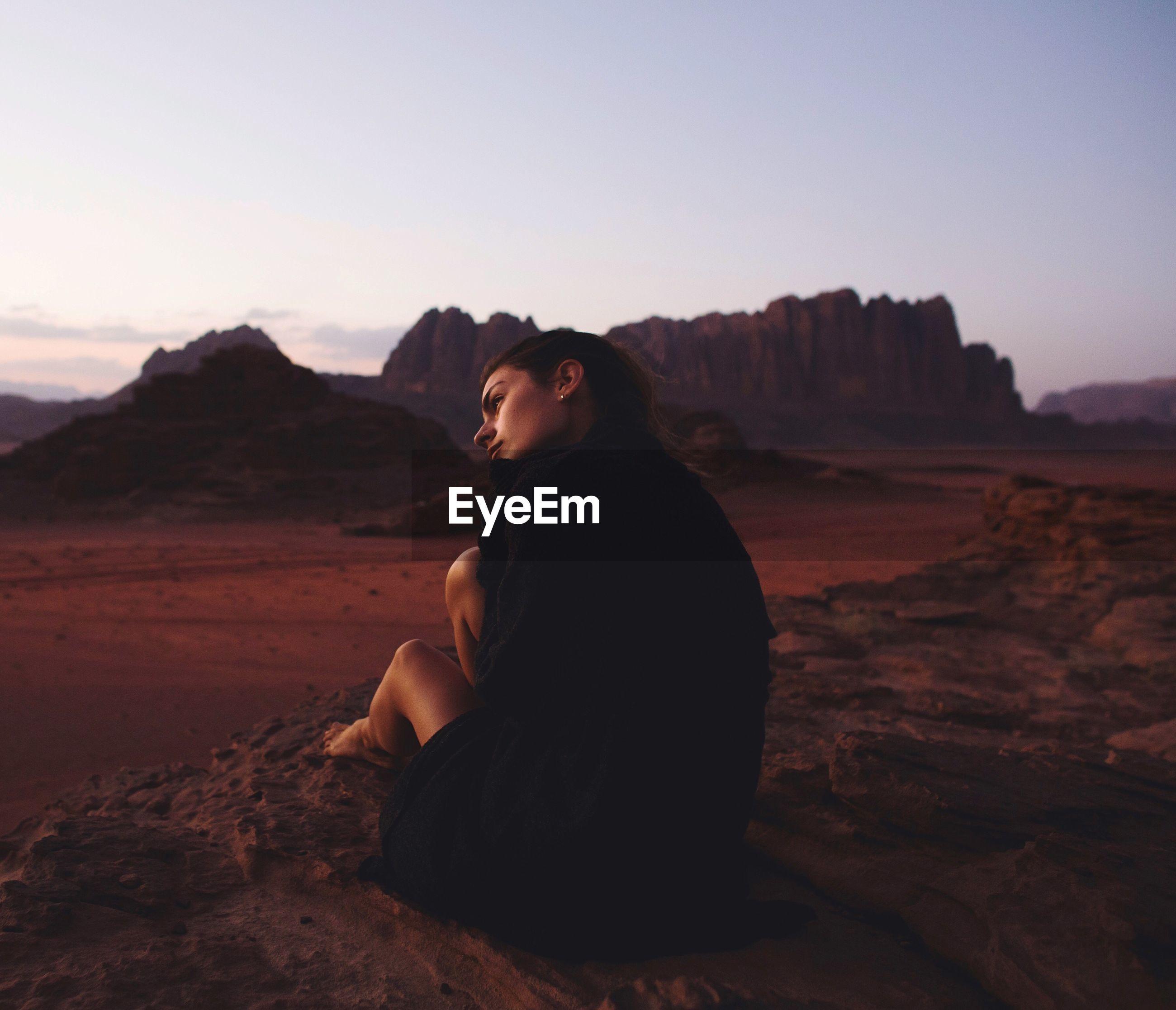 Woman sitting on rock in desert against clear sky