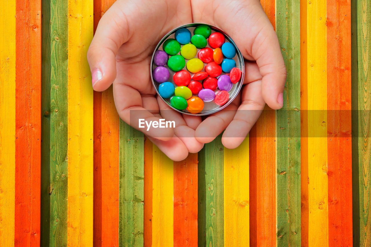 multi colored, childhood, human hand, human body part, holding, child, hand, wood - material, leisure activity, real people, candy, people, lifestyles, day, sweet food, sweet, directly above, body part, boys, finger