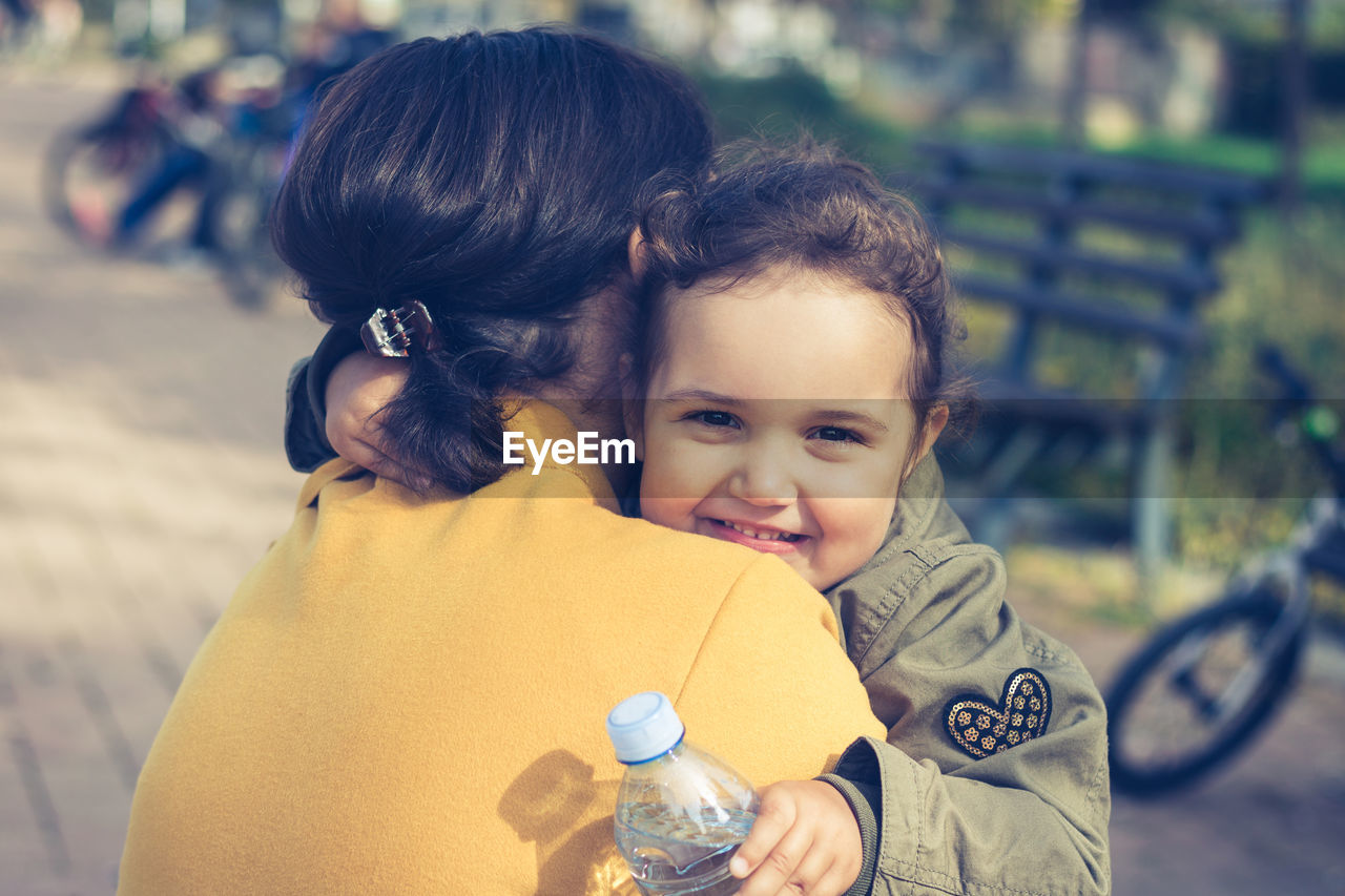 Portrait Of Cute Smiling Daughter Embracing Mother At Park
