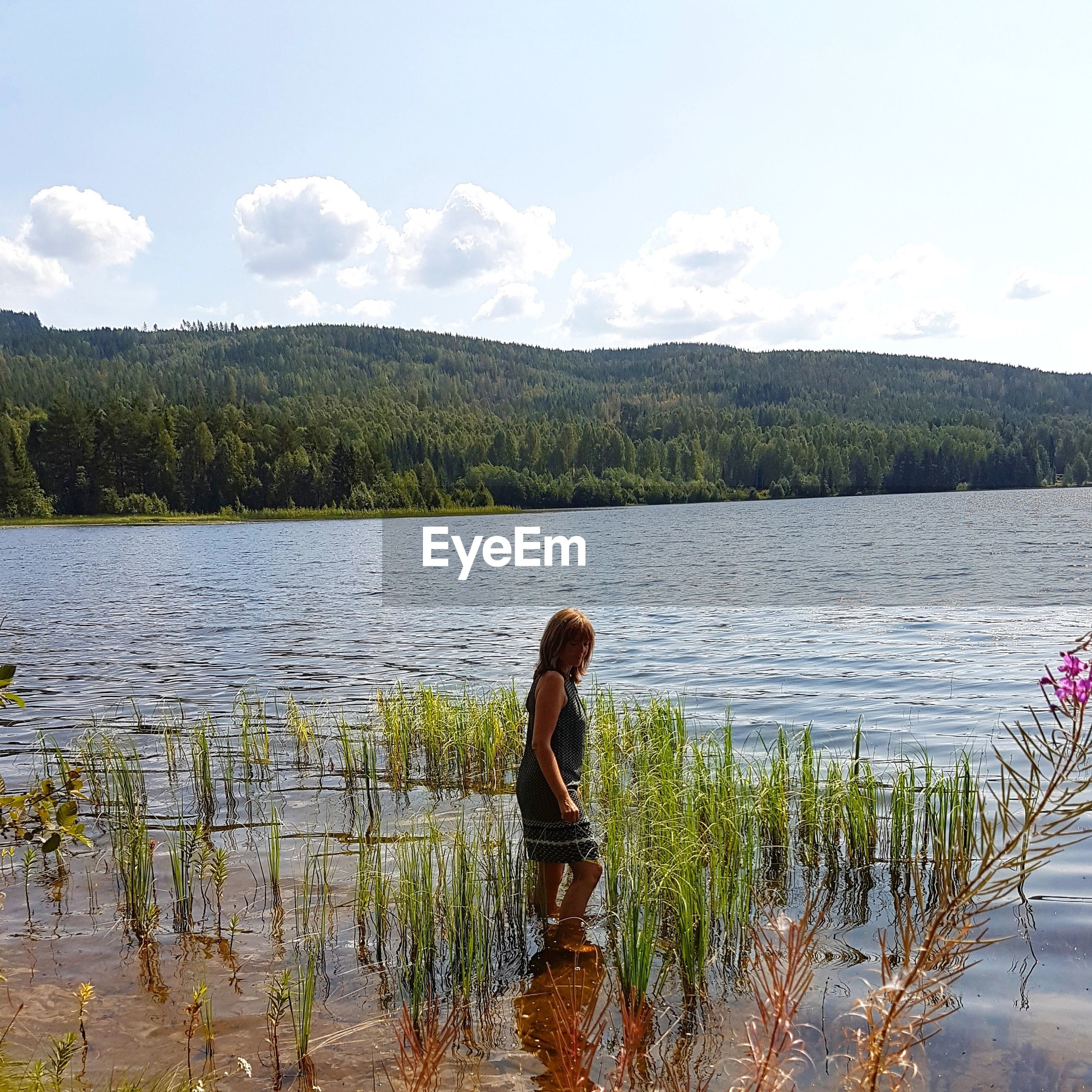 Side view of woman standing in lake against sky