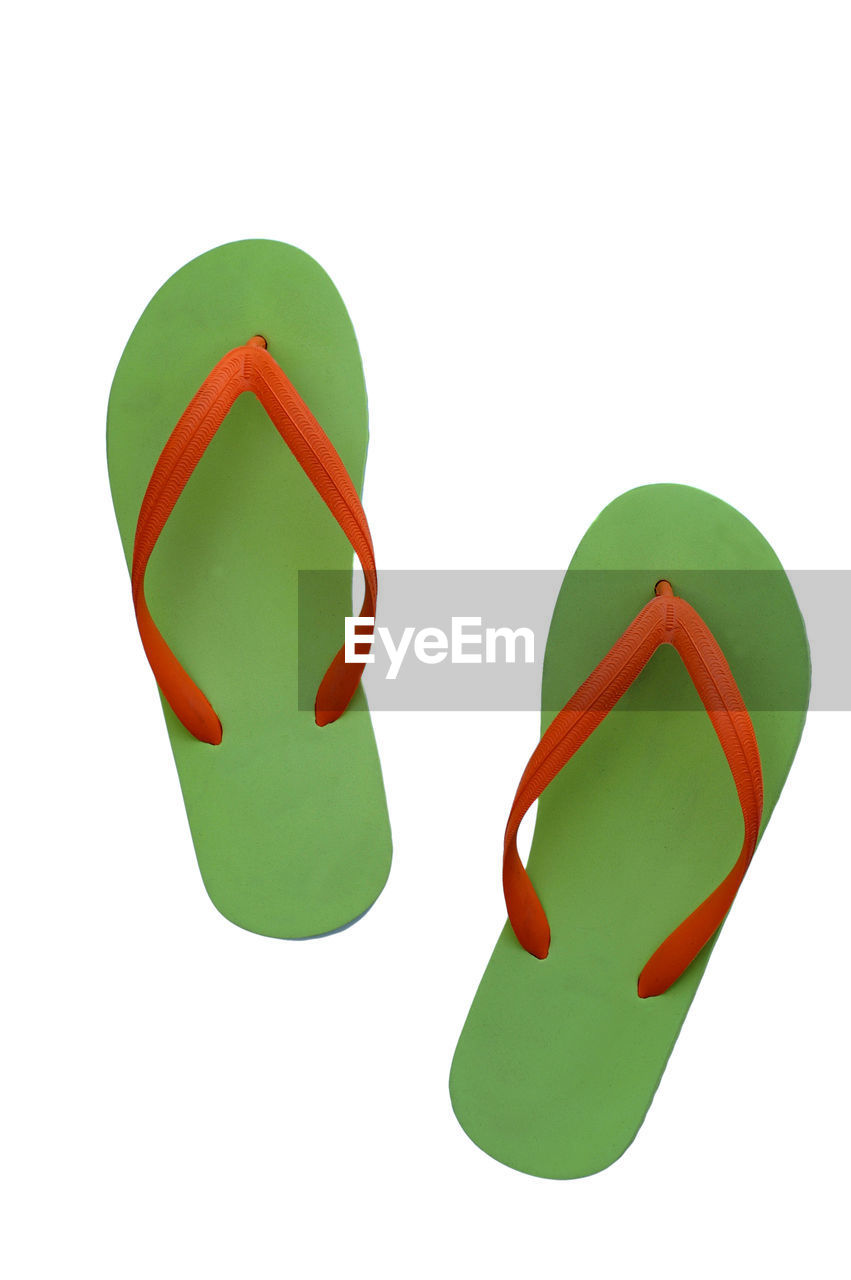 Close-Up Of Green Flip-Flops Over White Background