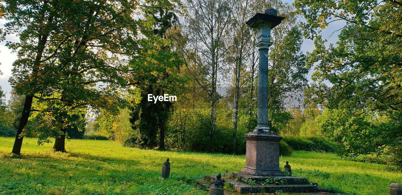 tree, plant, grass, nature, growth, green color, day, land, no people, beauty in nature, tranquility, architecture, grave, park, field, outdoors, tombstone, cemetery, tranquil scene, built structure