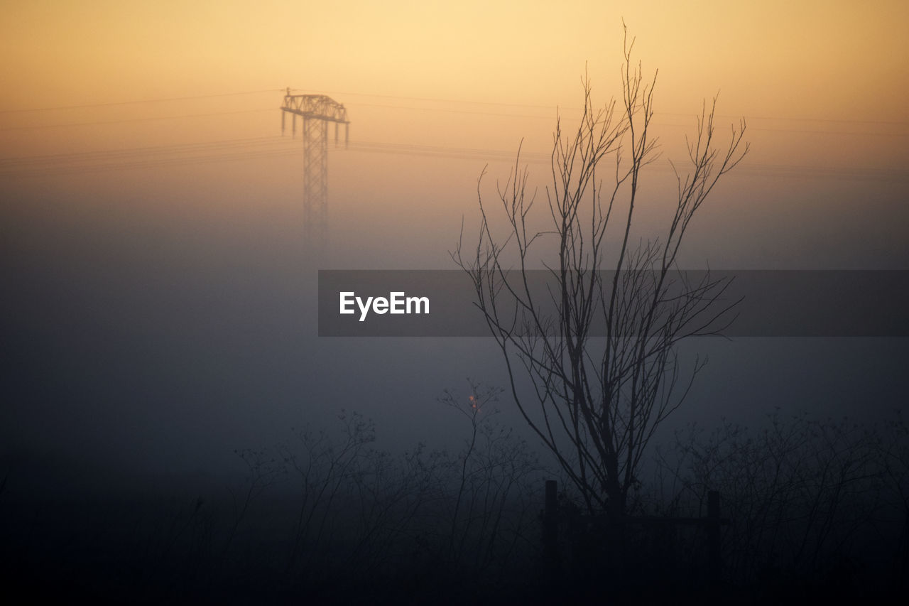 sunset, nature, outdoors, silhouette, tranquil scene, beauty in nature, tranquility, no people, lake, hazy, mist, scenics, sky, fog, water, electricity pylon, tree, bare tree, day