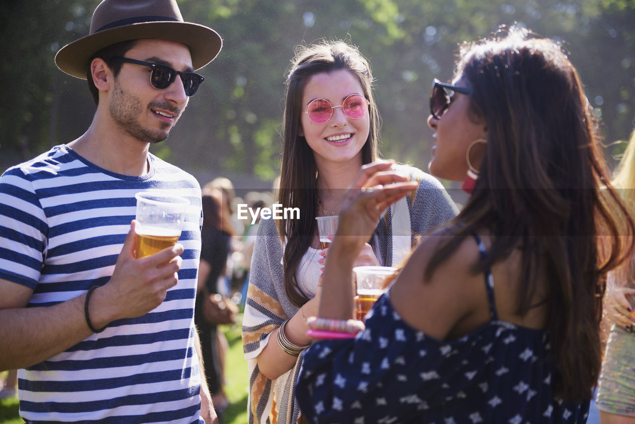sunglasses, drink, refreshment, friendship, young adult, alcohol, group of people, fashion, glasses, leisure activity, lifestyles, real people, food and drink, young men, waist up, casual clothing, smiling, standing, drinking, outdoors, hairstyle, glass