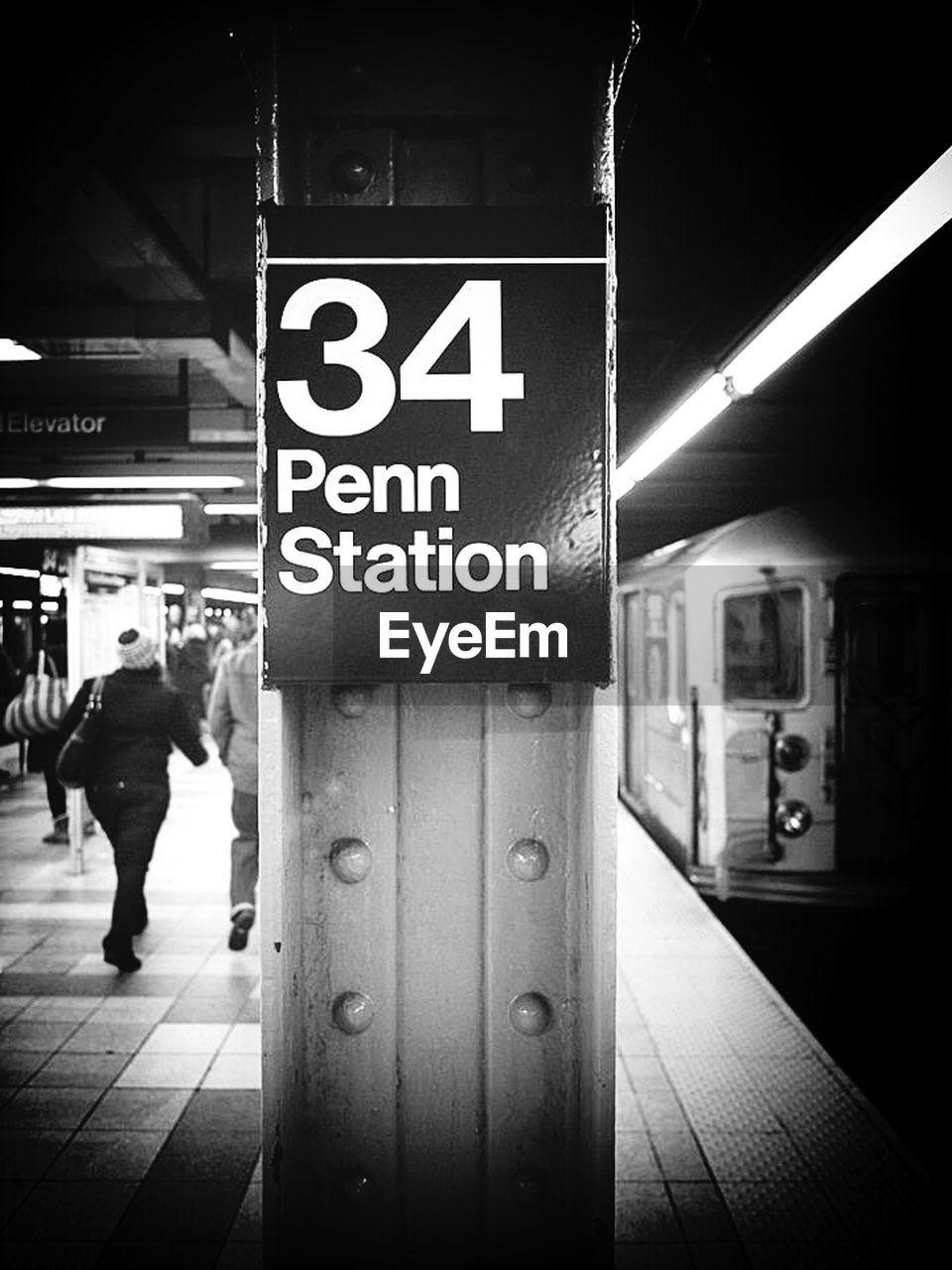 Text on metallic column with passengers walking on subway station