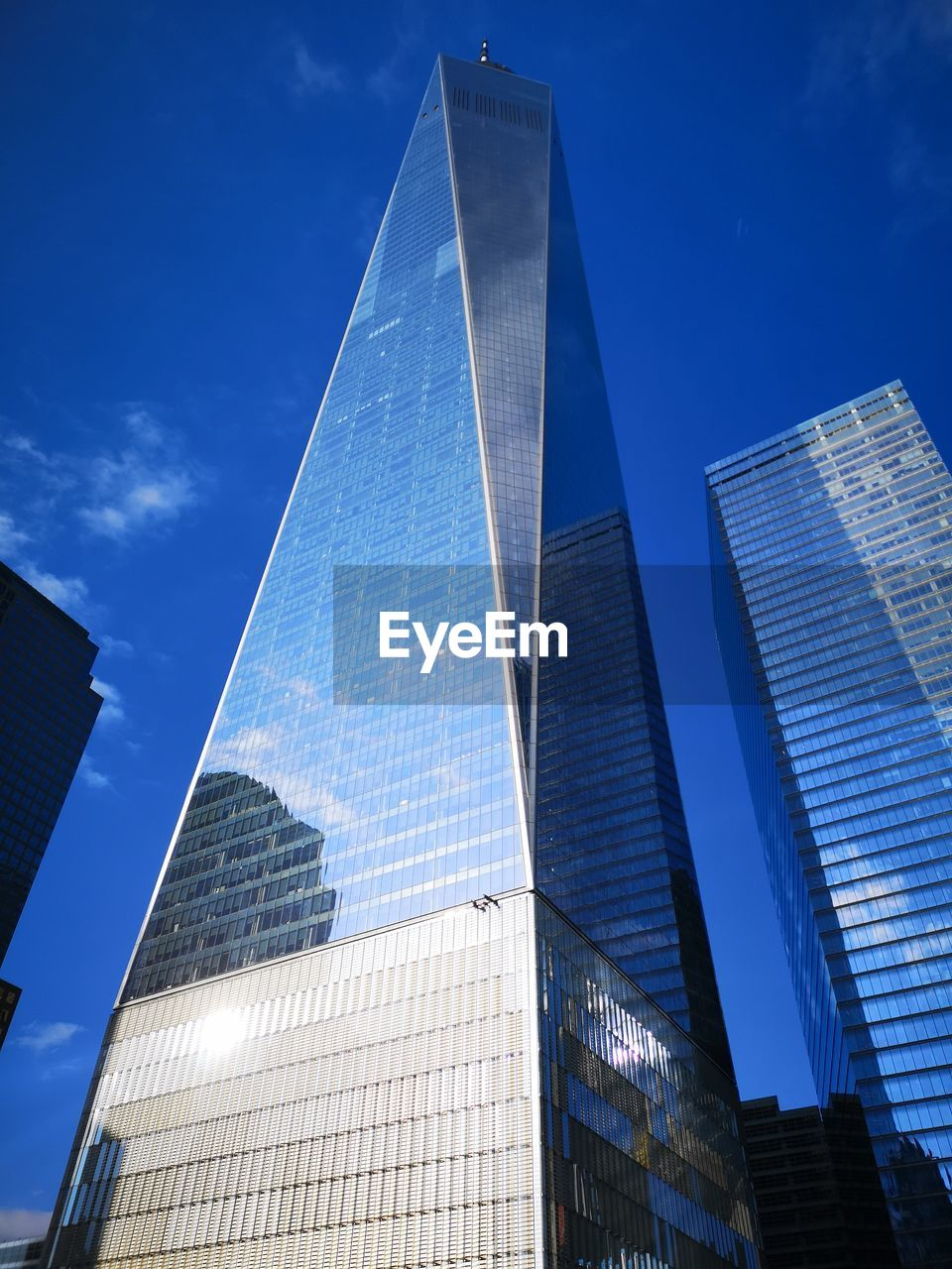 built structure, architecture, building exterior, office building exterior, tall - high, city, low angle view, modern, skyscraper, building, sky, office, glass - material, tower, nature, no people, blue, travel destinations, sunlight, outdoors, financial district