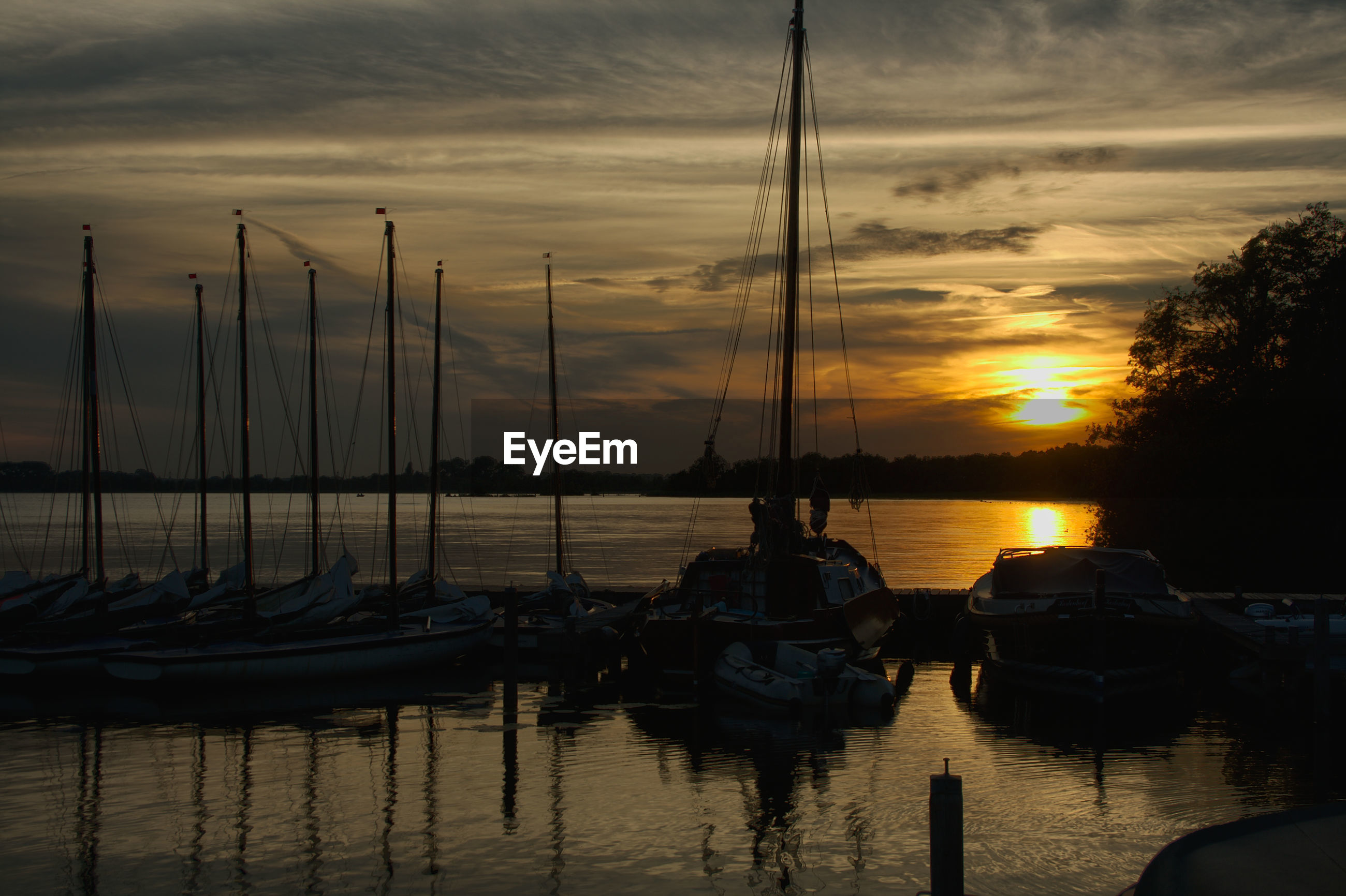 SAILBOATS MOORED ON SEA DURING SUNSET