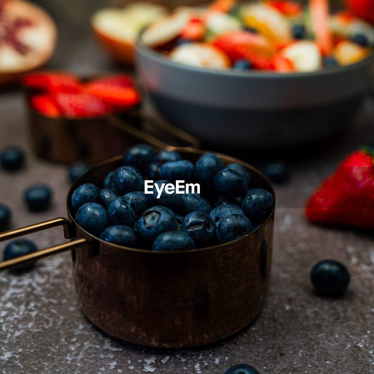 Close-up of blueberries in measuring cup on table with assortment of fruit