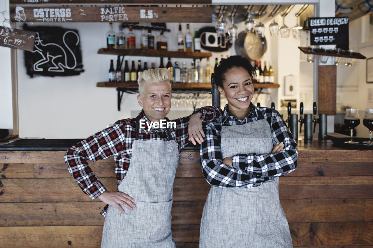 looking at camera, two people, portrait, smiling, togetherness, standing, indoors, front view, happiness, emotion, real people, child, men, people, males, adult, casual clothing, apron, waist up, women, hairstyle, teenager