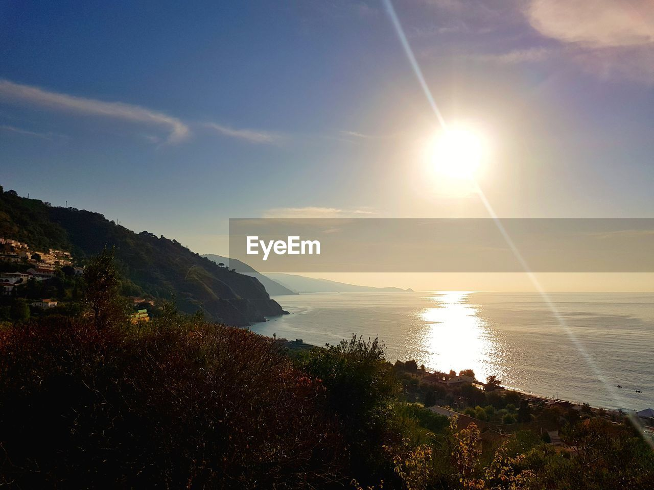 sky, water, beauty in nature, scenics - nature, sunlight, tranquility, sun, tranquil scene, sea, nature, sunbeam, mountain, lens flare, plant, no people, cloud - sky, idyllic, land, beach, bright, outdoors