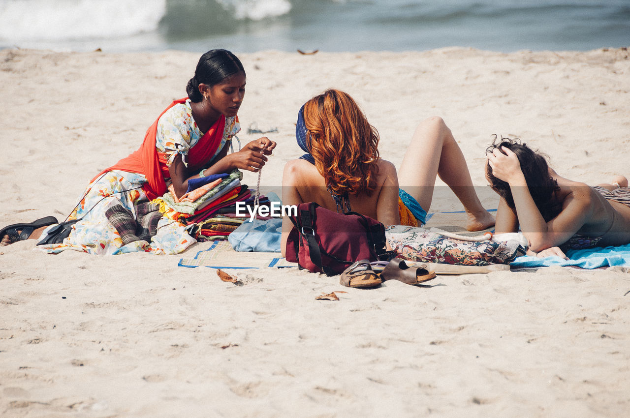 FRIENDS RELAXING ON SAND