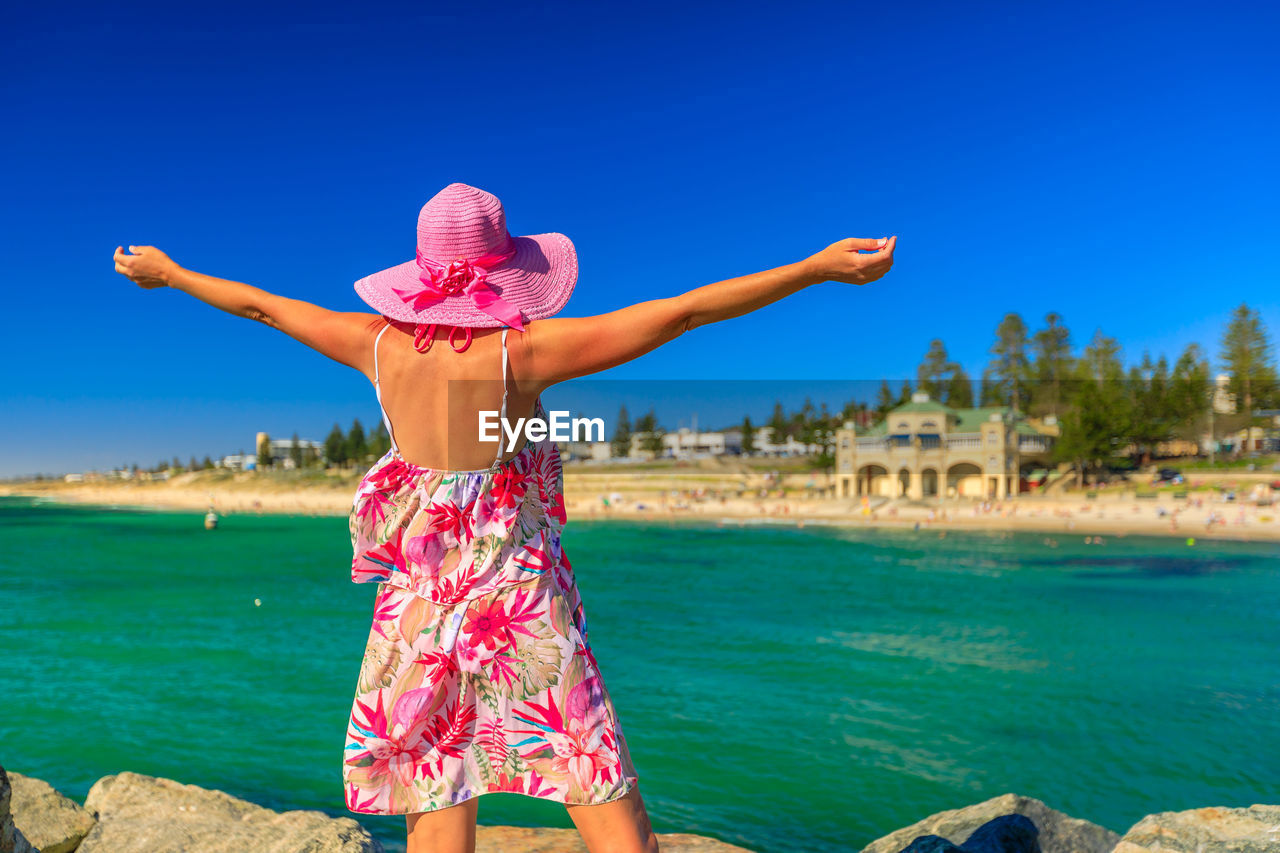water, one person, leisure activity, real people, lifestyles, arms outstretched, nature, sky, rear view, day, human arm, sunlight, women, limb, clothing, sea, blue, beauty in nature, pink color, outdoors