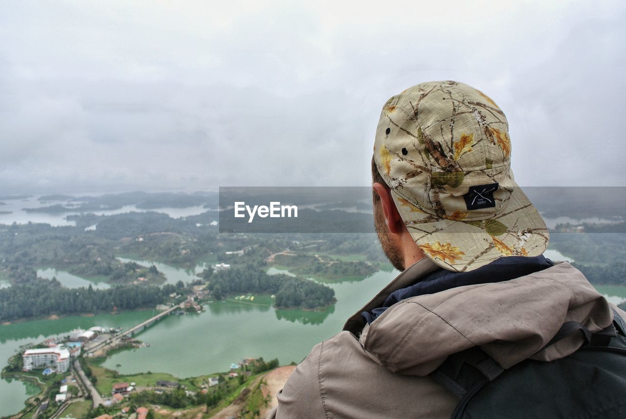 HIGH ANGLE VIEW OF MAN LOOKING AT MOUNTAIN
