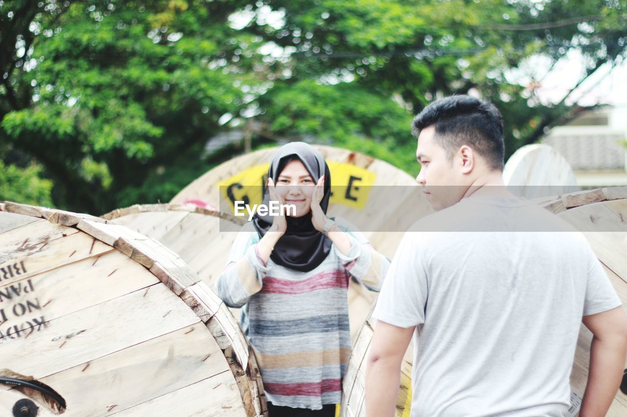 Portrait Of Young Woman With Boyfriend Standing By Cable Drums