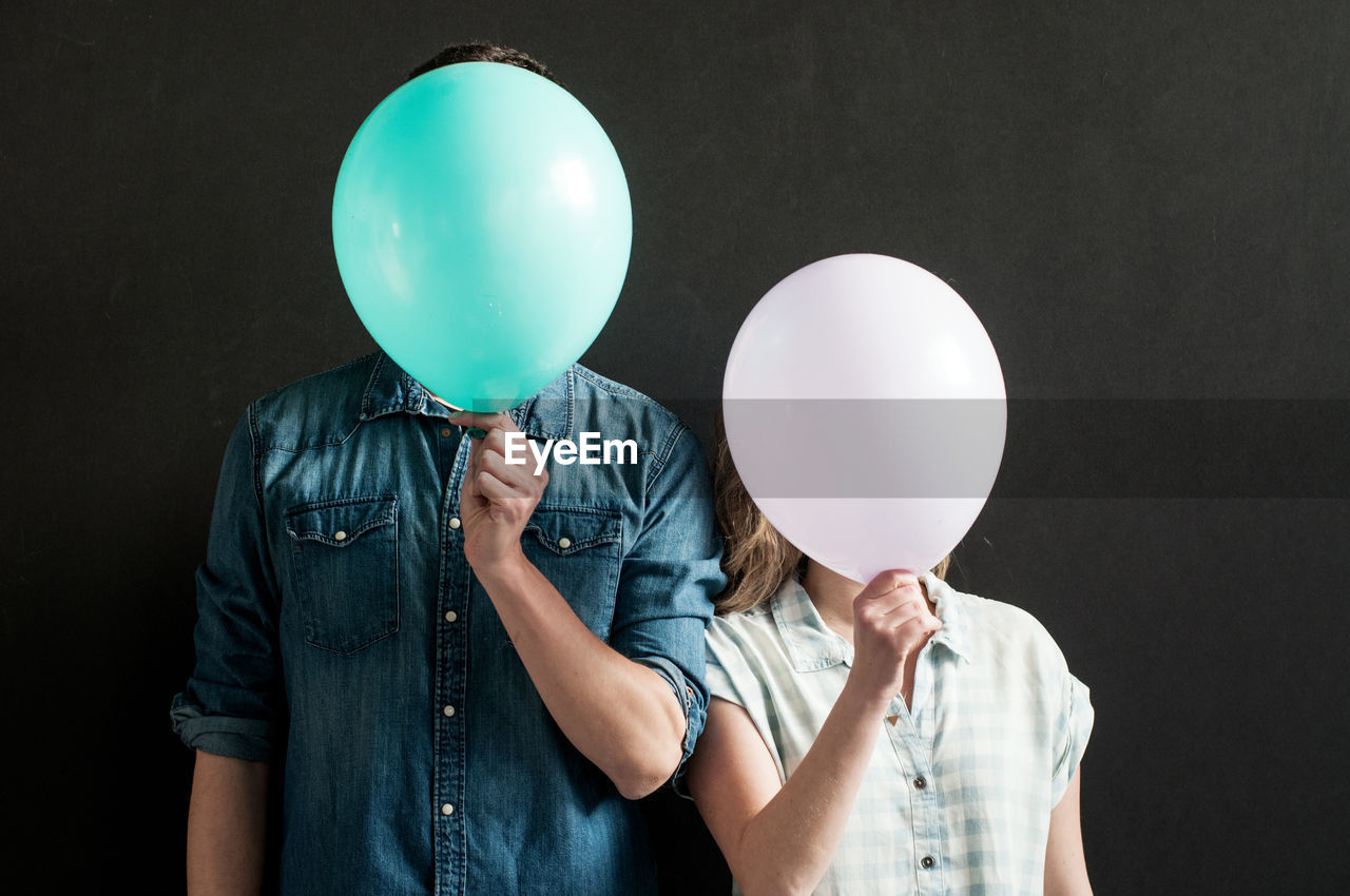 Portrait of people holding balloons
