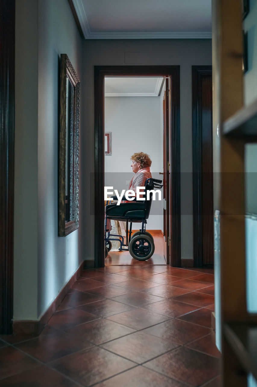 Woman Sitting On Wheelchair At Home