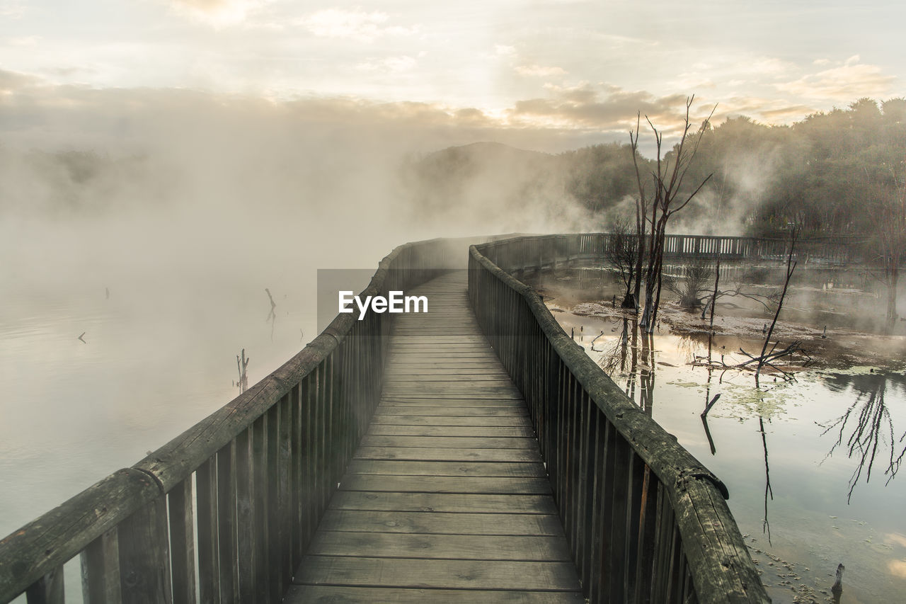 the way forward, water, fog, railing, direction, beauty in nature, nature, tranquil scene, connection, tranquility, scenics - nature, wood - material, bridge, no people, sky, non-urban scene, built structure, architecture, bridge - man made structure, outdoors, footbridge