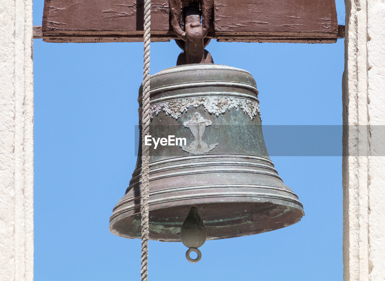 low angle view, hanging, bell, built structure, outdoors, day, clear sky, no people, architecture, blue, building exterior, close-up, bell tower, sky