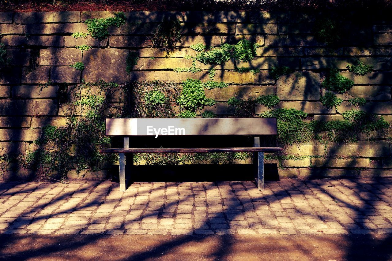 Empty bench against wall at park