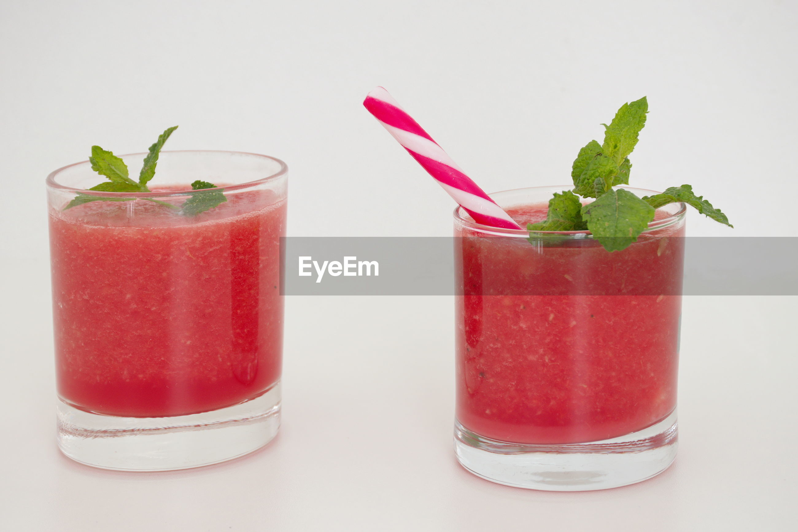 Smoothie of watermelon with mint leaves against the white background