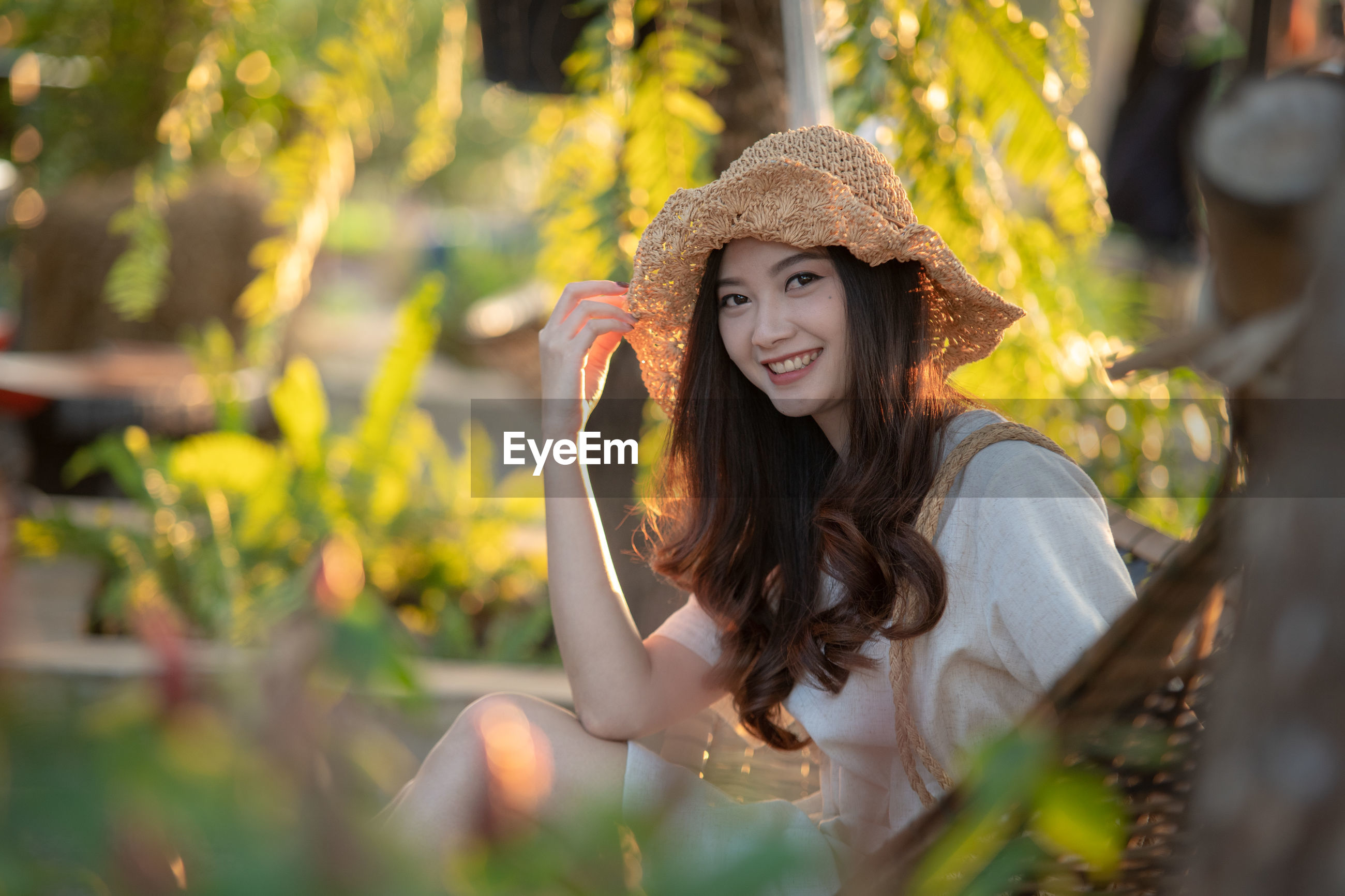 Portrait of smiling young woman wearing hat against plants