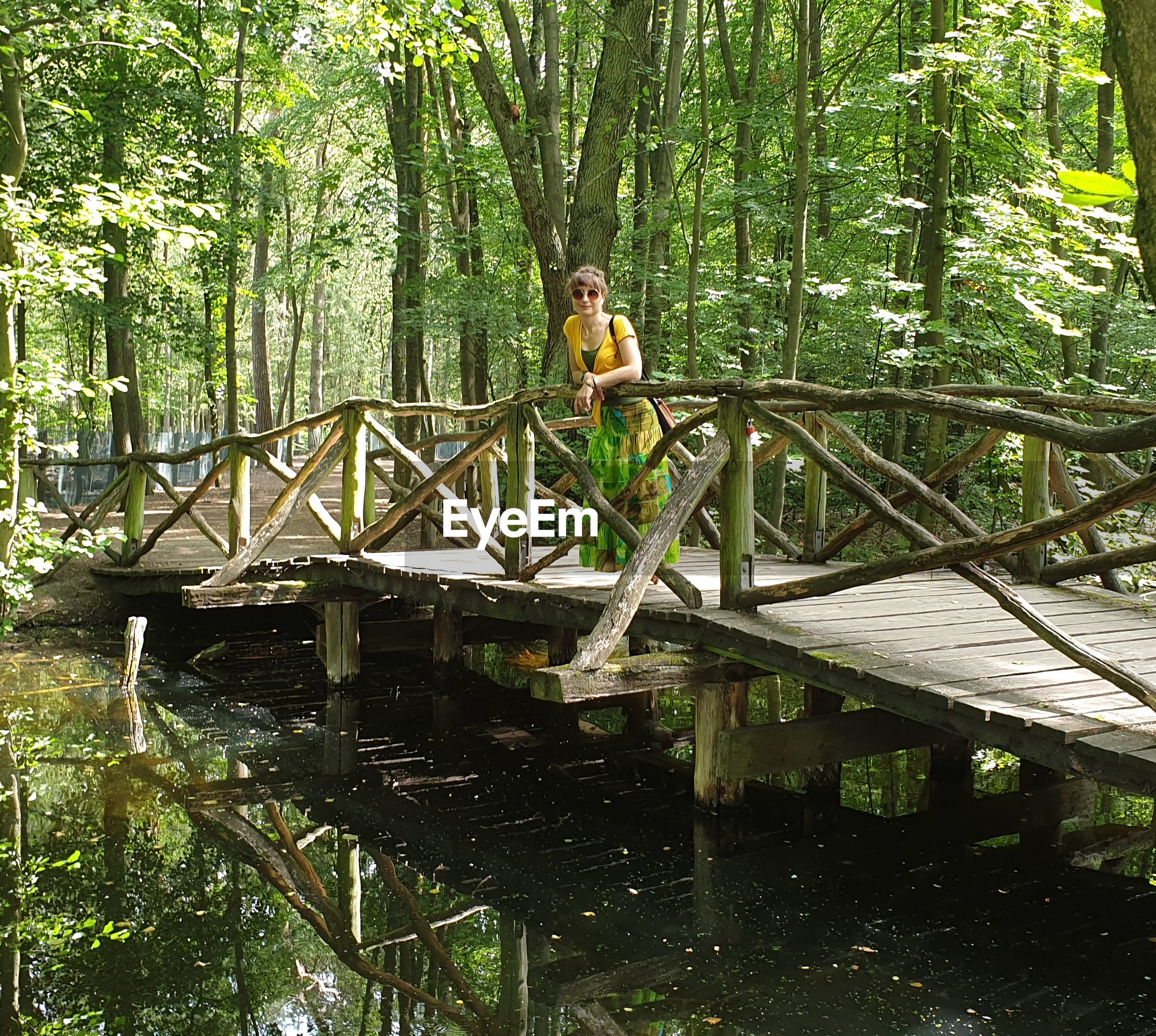 Woman standing on bridge in forest