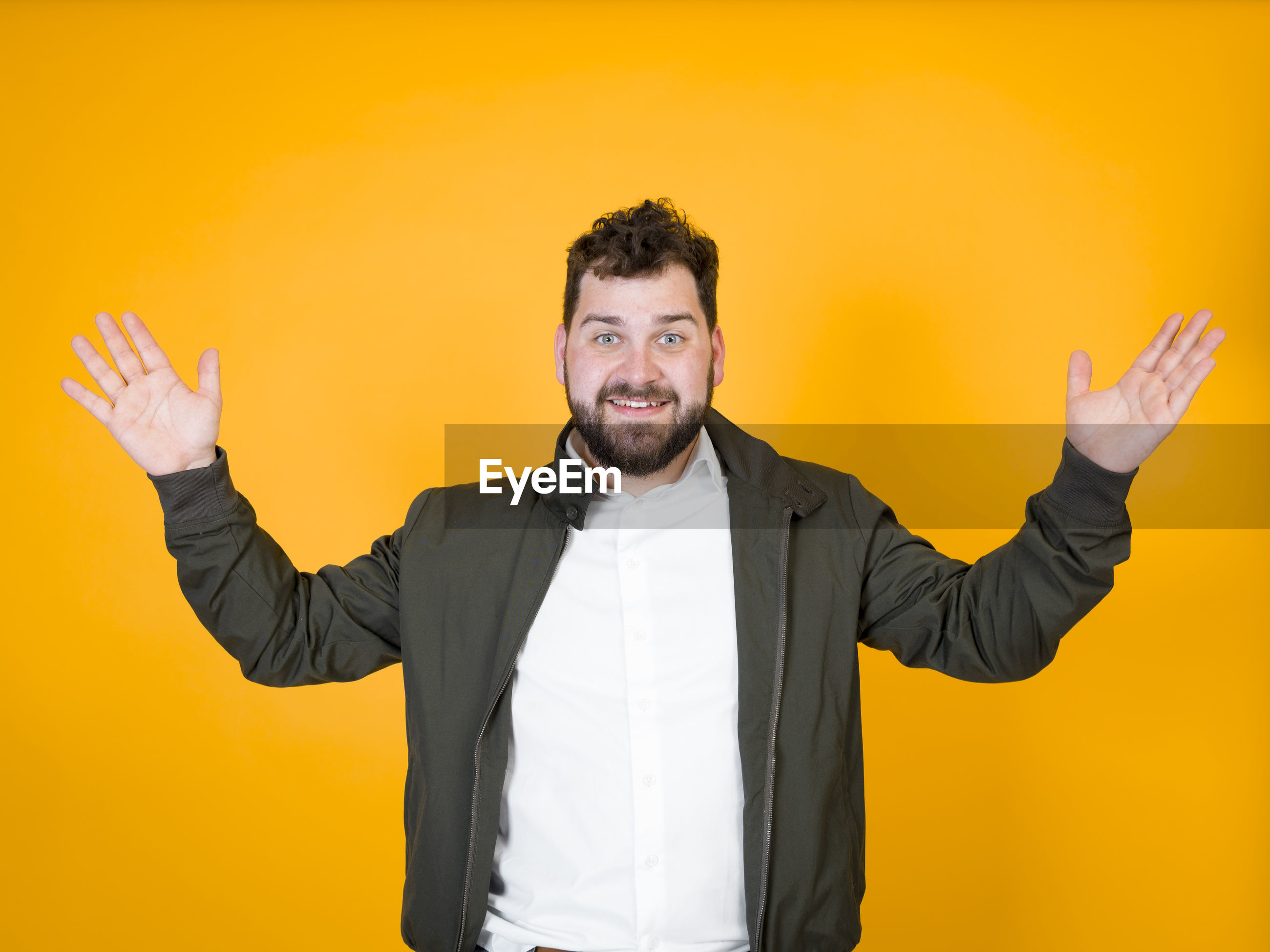Portrait of young man smiling while standing against yellow background
