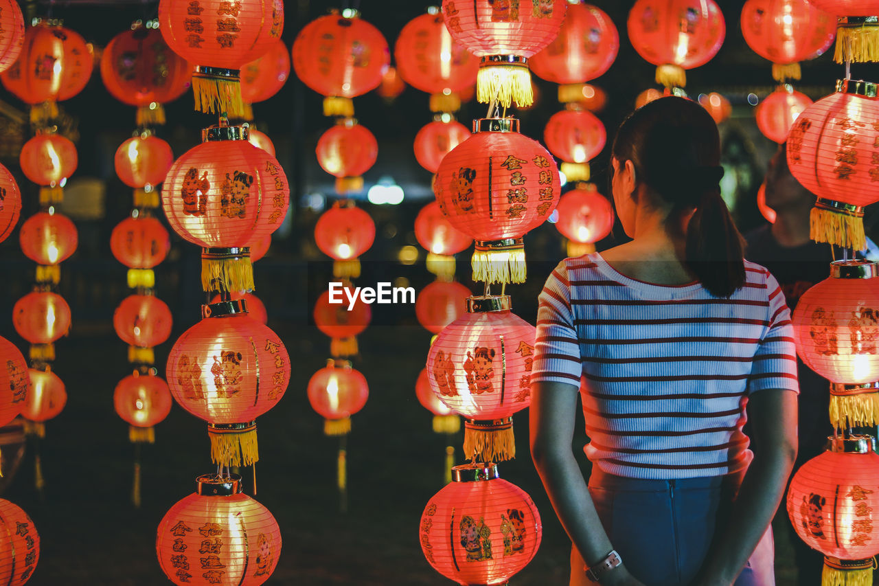 Rear view of woman standing against illuminated red lanterns hanging at night