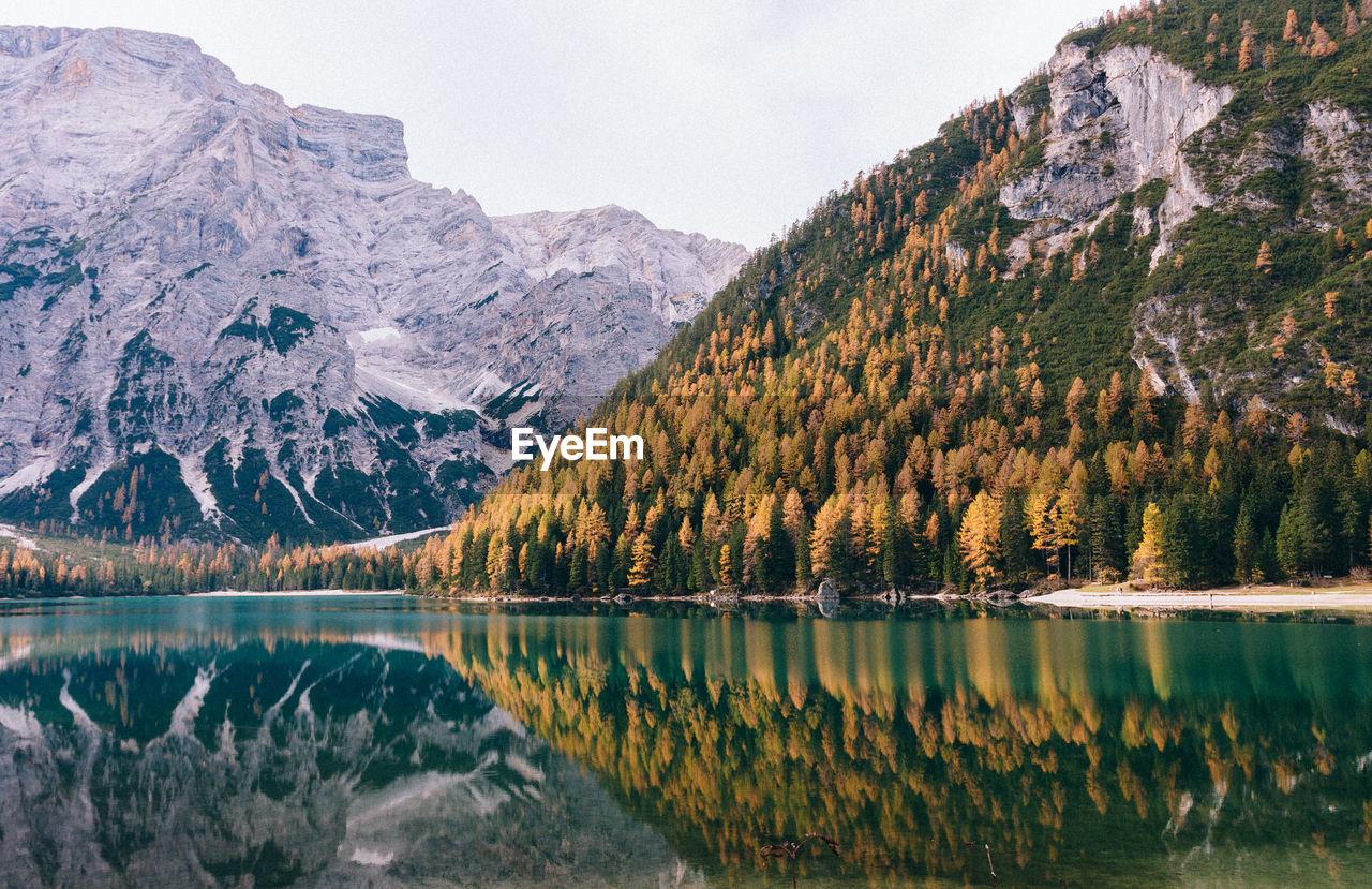 Autumn trees and mountain reflecting on calm lake