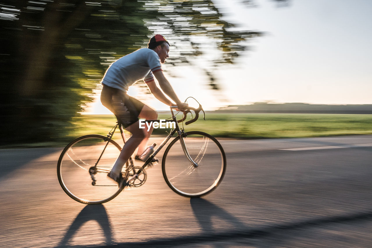 Blurred Motion Of Man Riding Bicycle On Road During Sunny Day