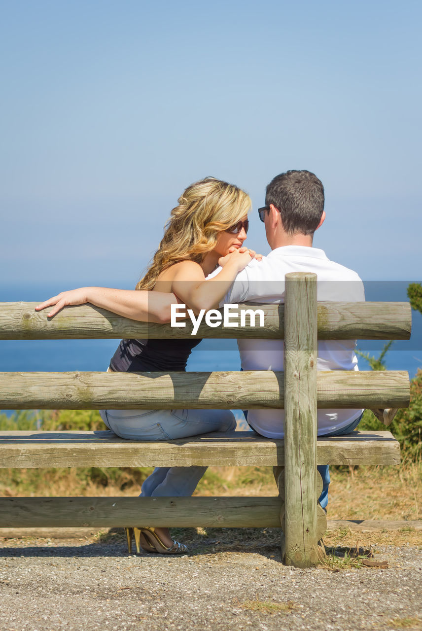 View of couple sitting on bench against sky