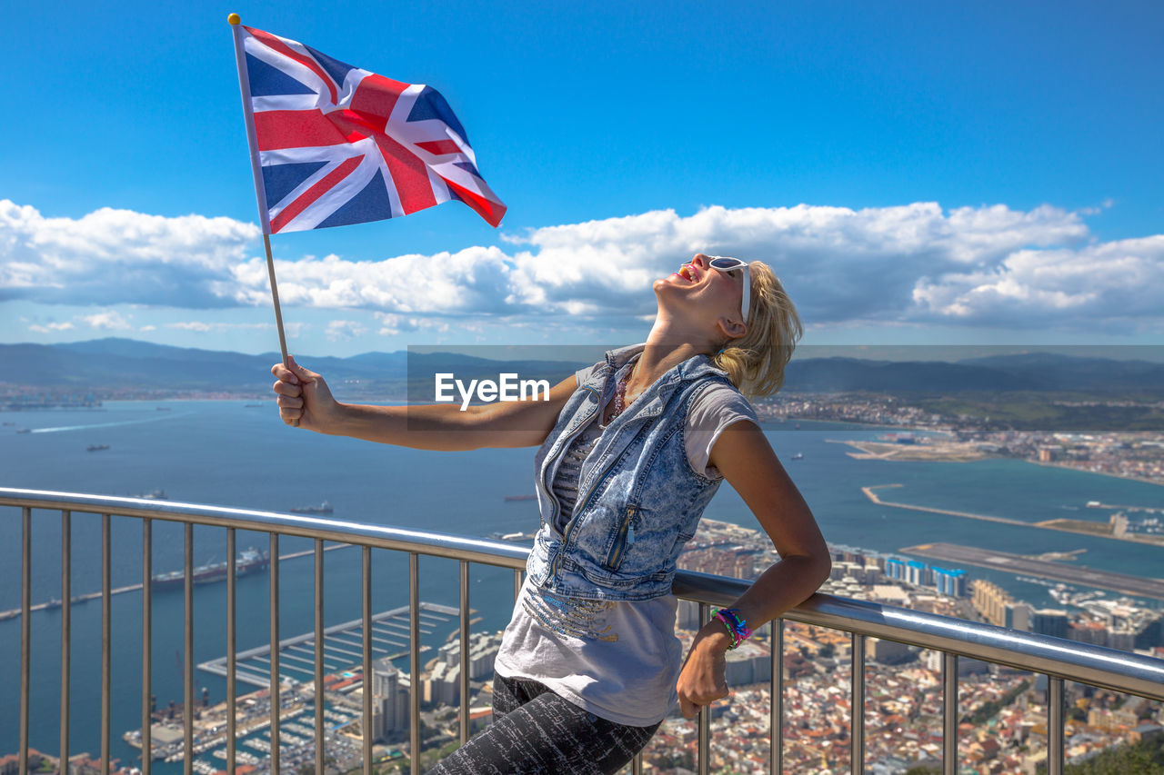 Happy Woman With British Flag Standing At Observation Point Against Blue Sky