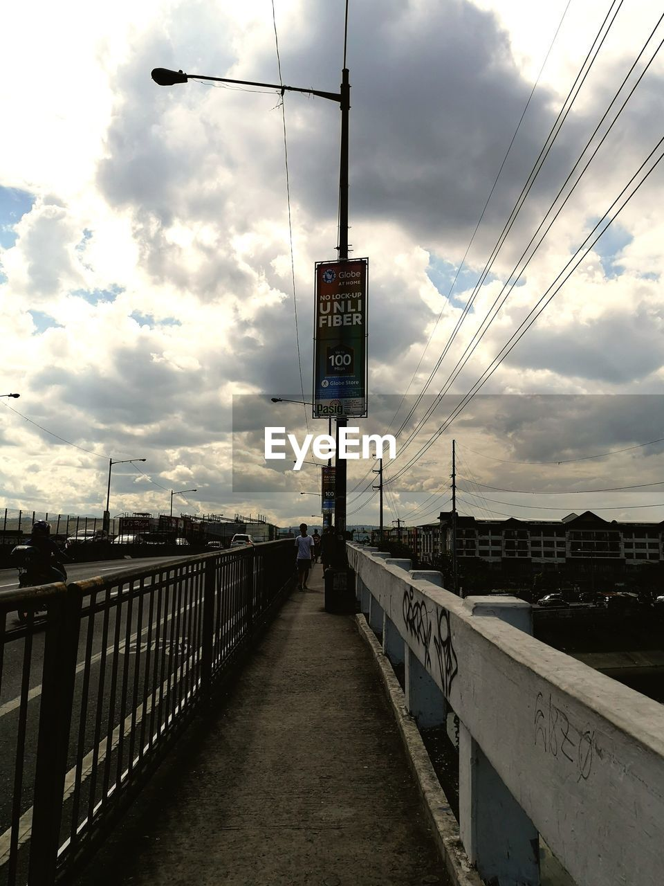 cloud - sky, communication, sky, sign, text, architecture, western script, direction, built structure, connection, transportation, information, nature, railing, the way forward, road, information sign, no people, outdoors, guidance, electricity