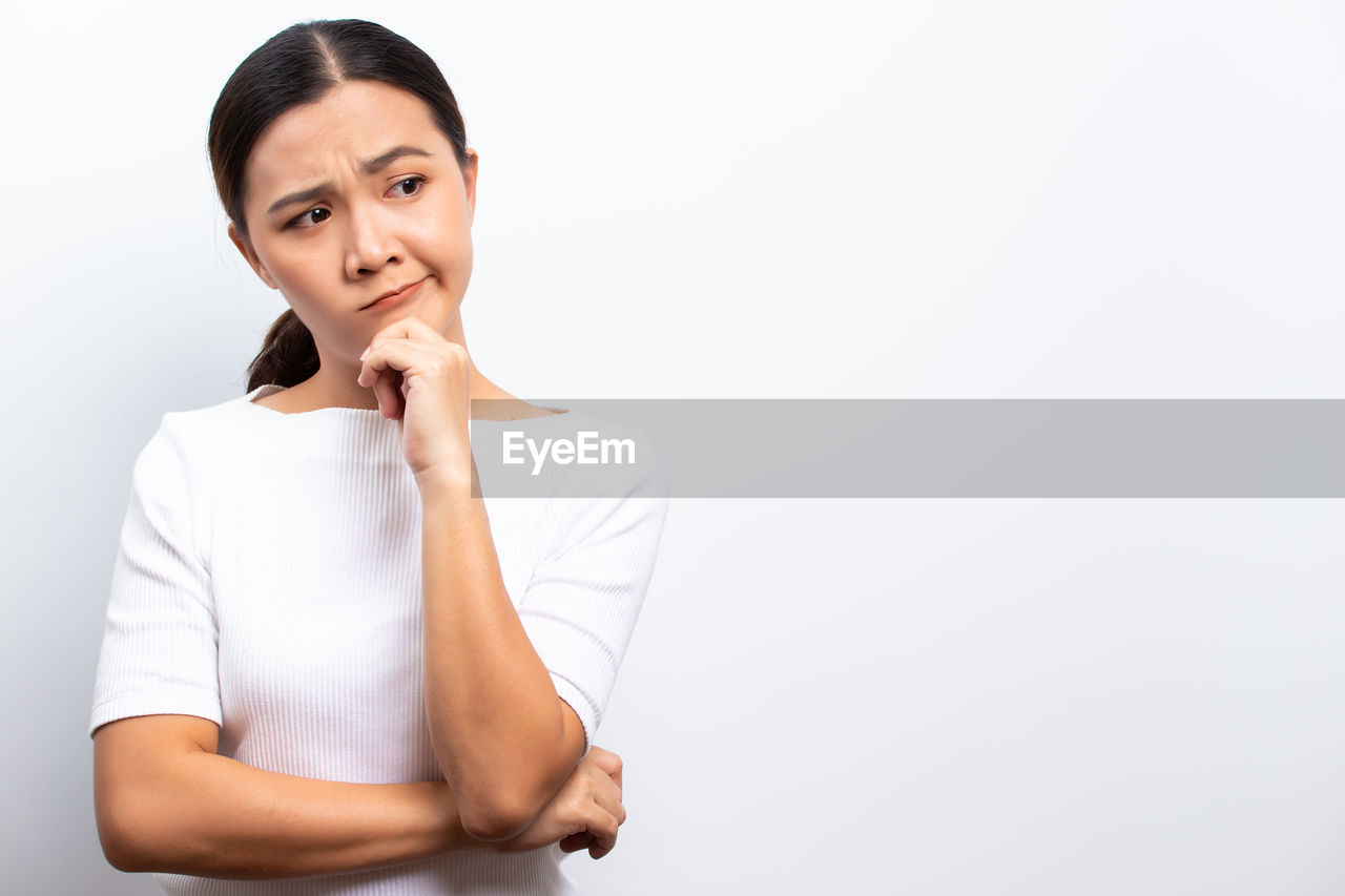 Angry woman standing against white background