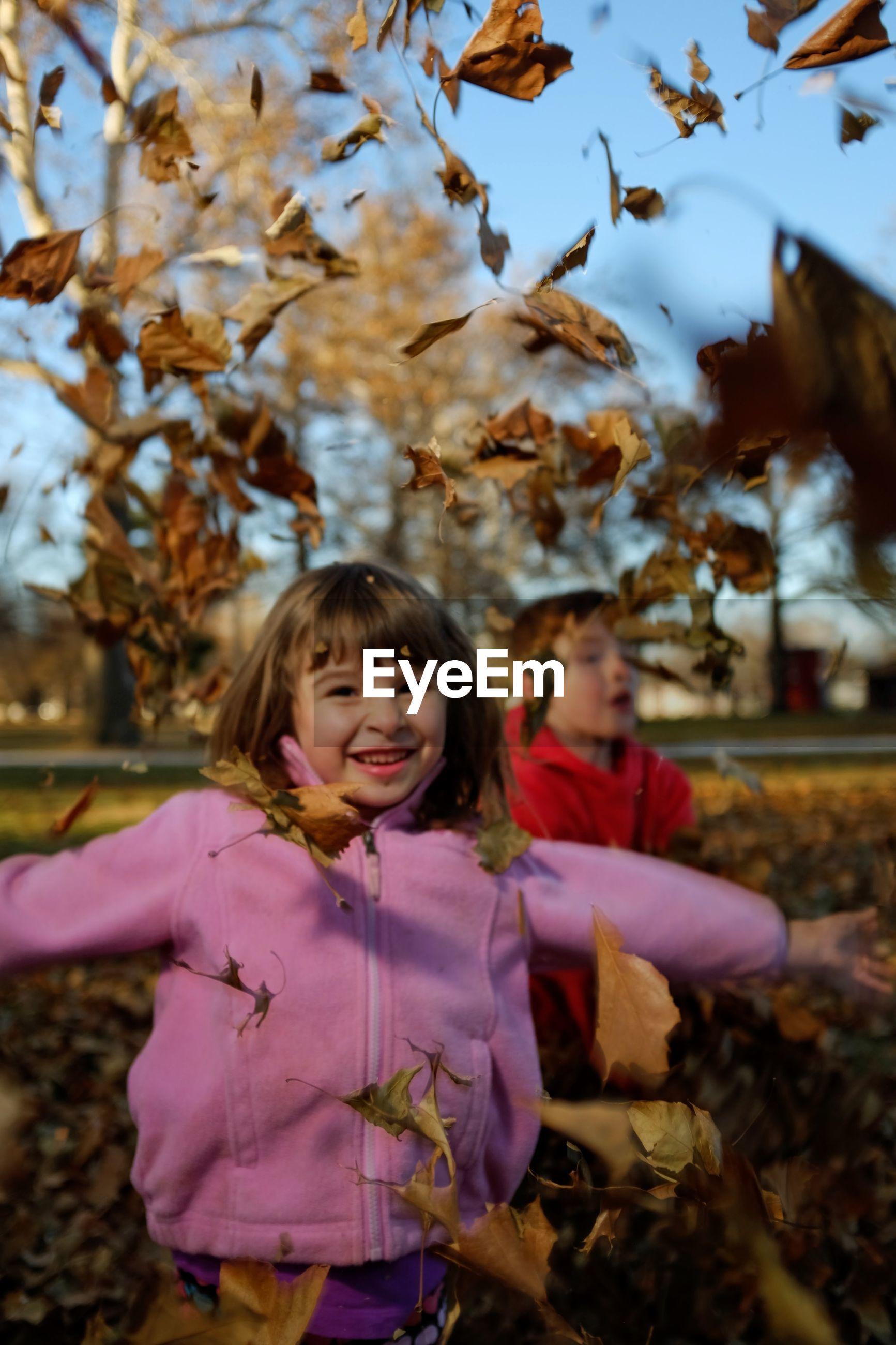 Full length portrait of girl throwing leaves on field