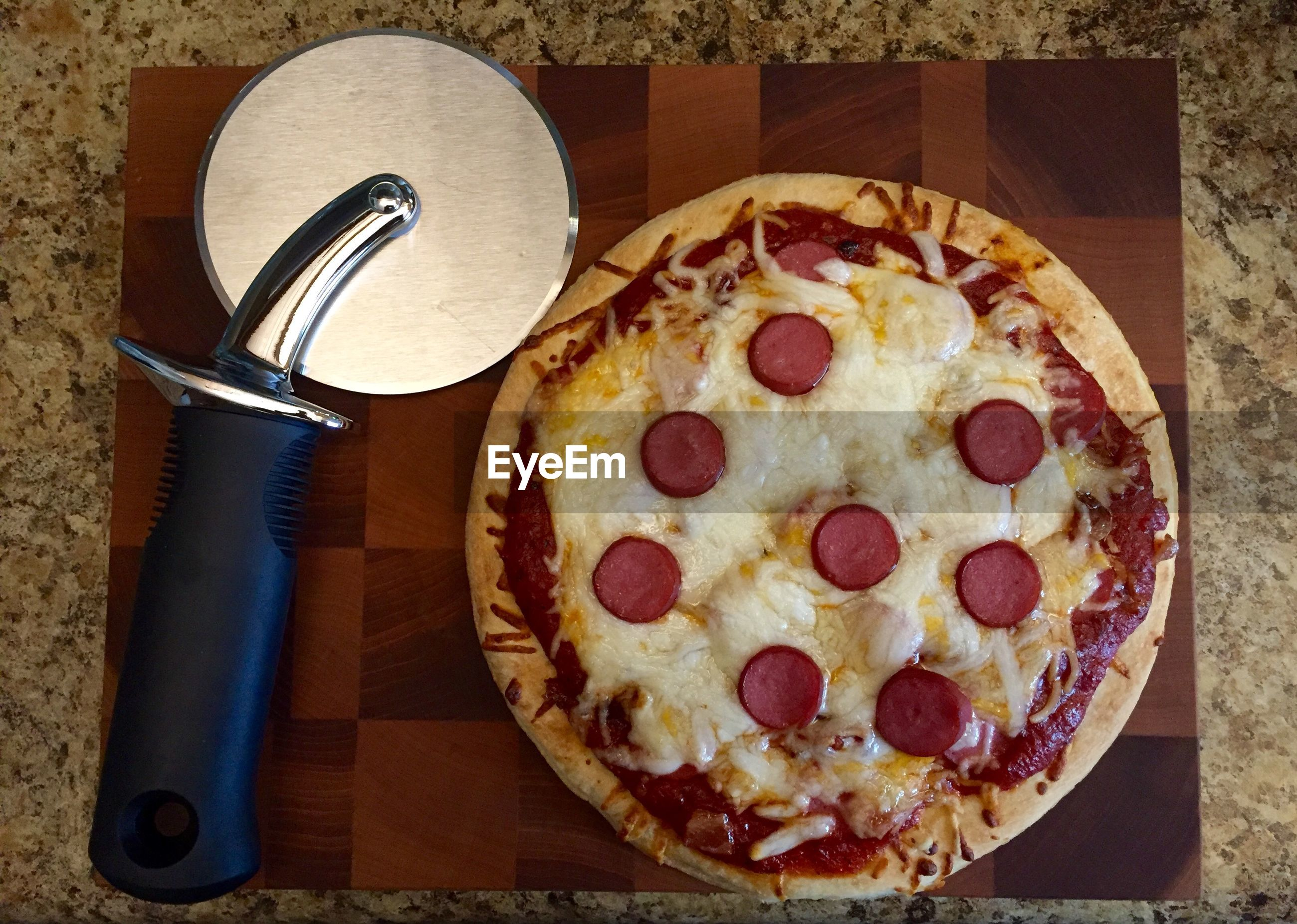 Directly above shot of pepperoni pizza with cutter on cutting board