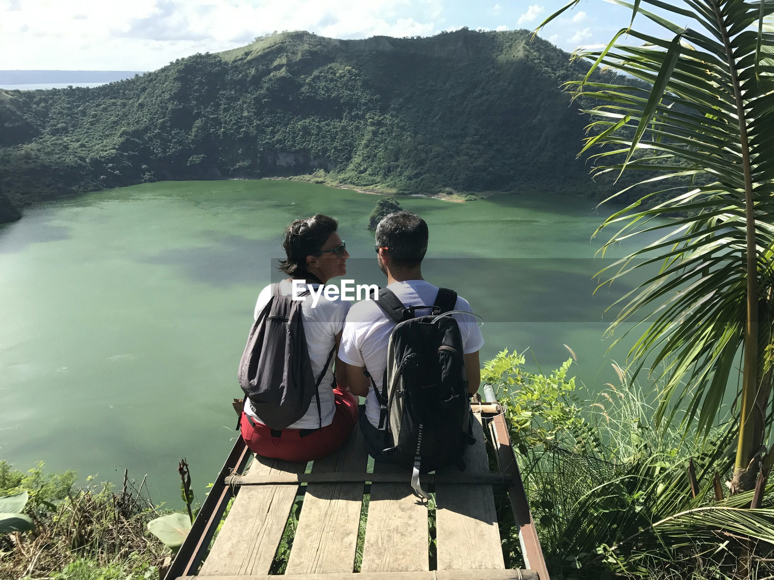 Rear view of couple sitting on observation point by lake