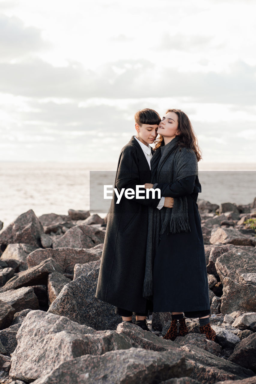 Lesbian women embracing while standing on rock against sea and sky