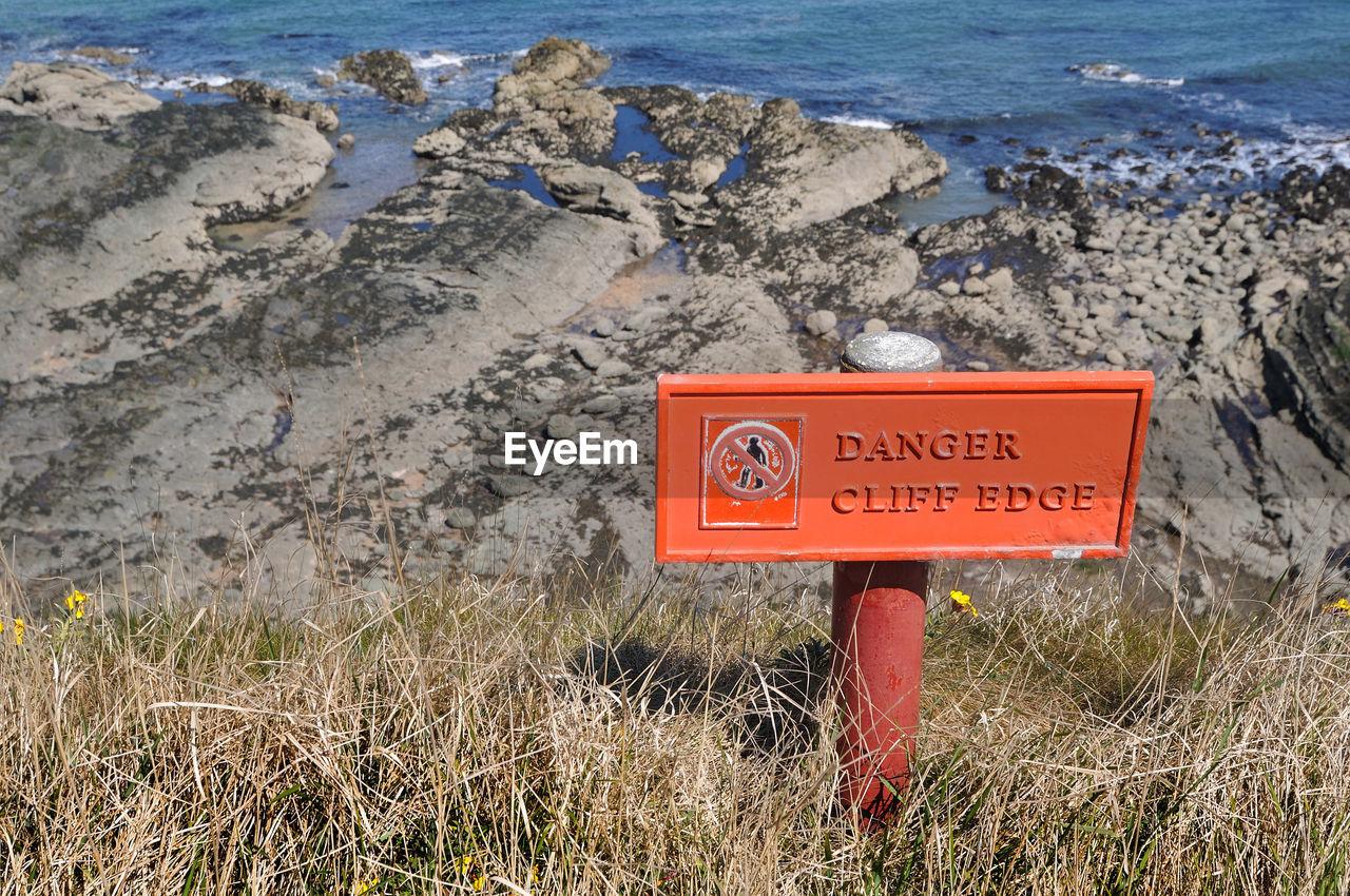 CLOSE-UP OF WARNING SIGN ON LAND
