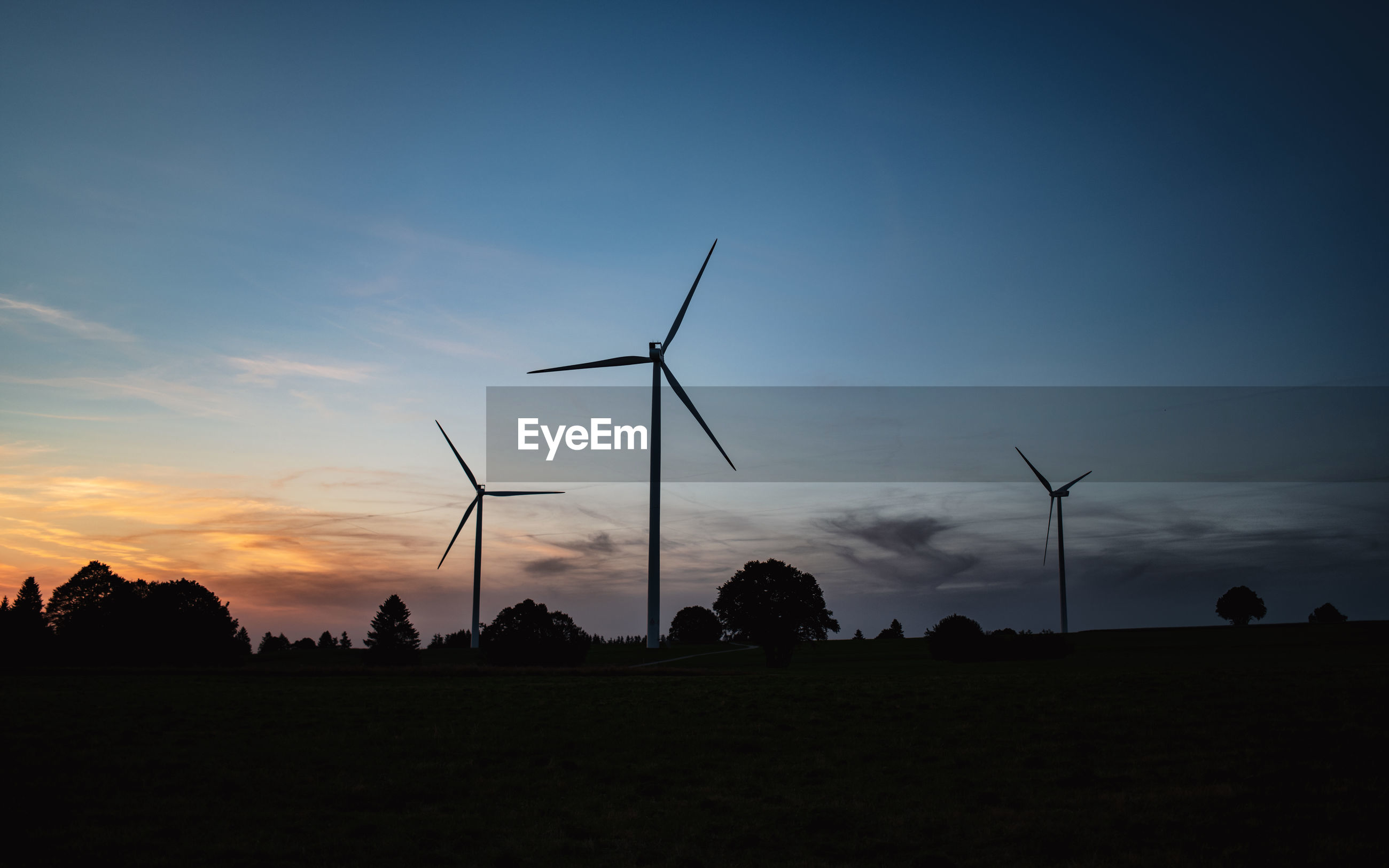Silhouette wind turbines on field against sky during dusk