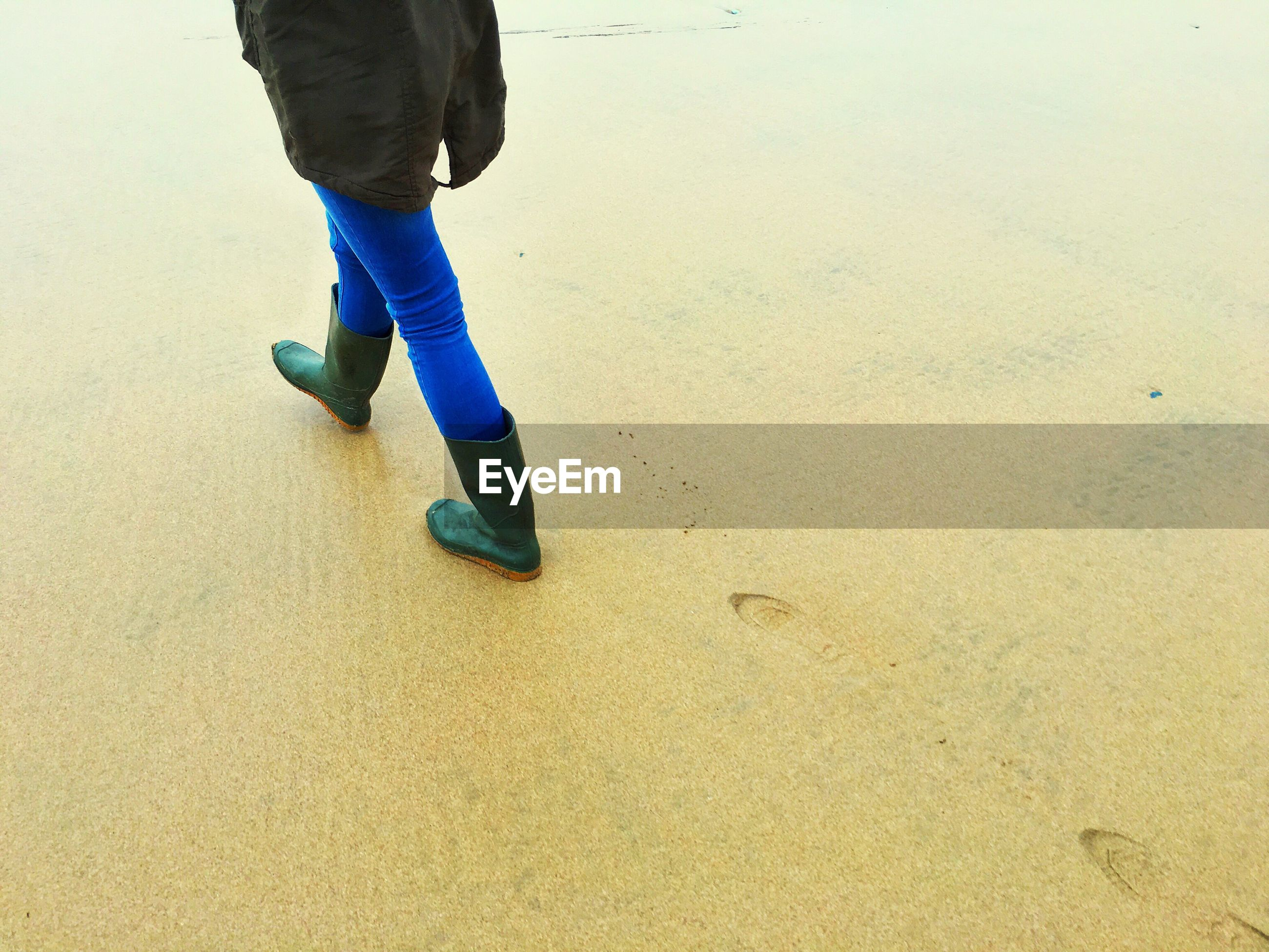 Low section of person walking on shore