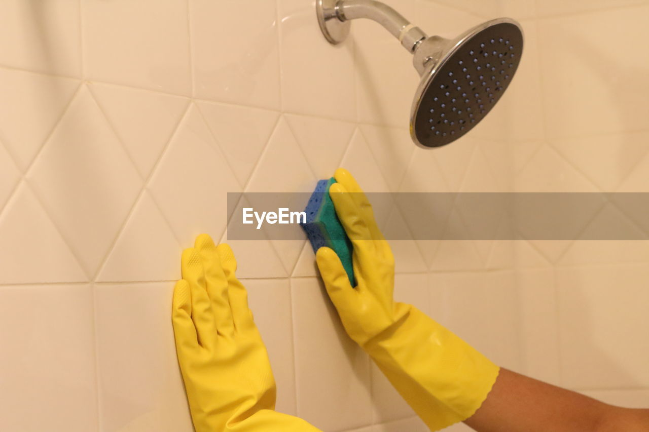 Cropped Hands Of Woman Cleaning Wall In Bathroom