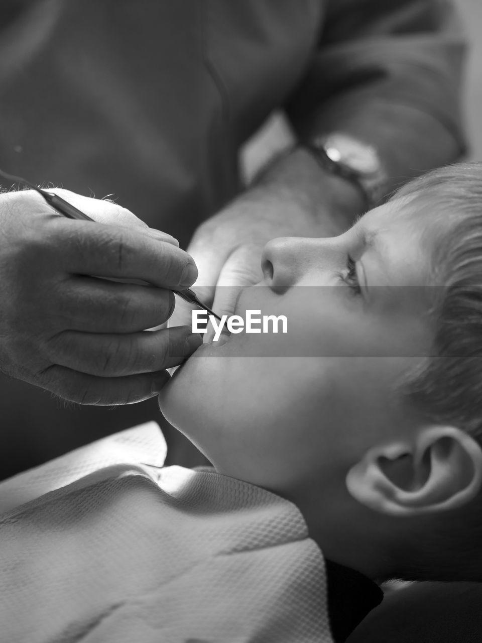 Close-up of dentist examining teeth of boy at clinic