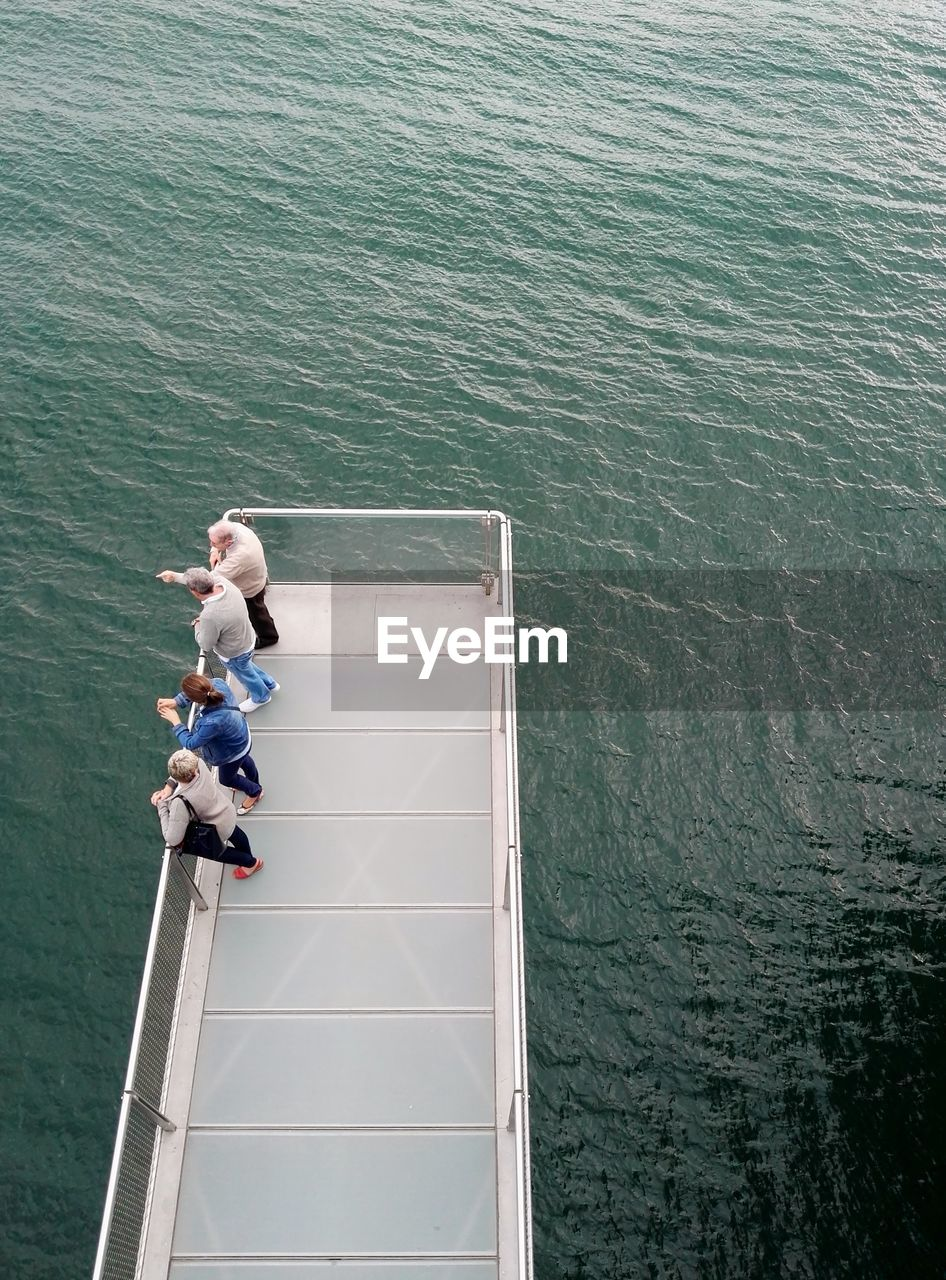 High angle view of people standing on pier over sea
