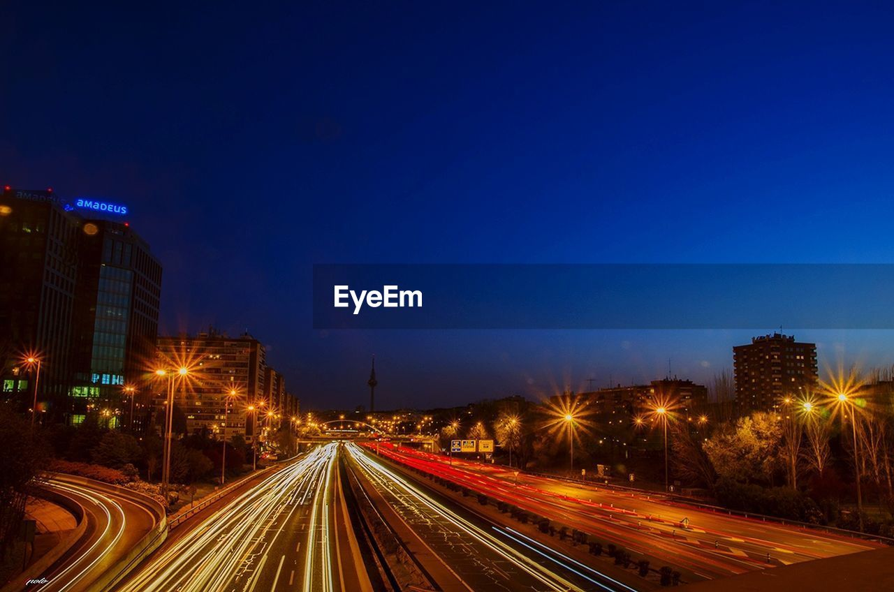 illuminated, night, light trail, transportation, speed, street light, architecture, long exposure, building exterior, city, city life, motion, built structure, road, outdoors, blue, no people, clear sky, high street, cityscape, sky
