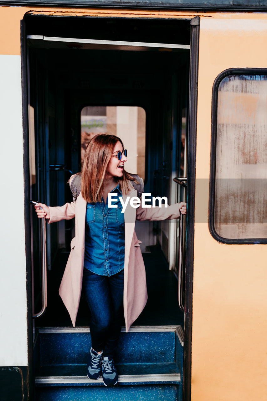 WOMAN STANDING BY TRAIN