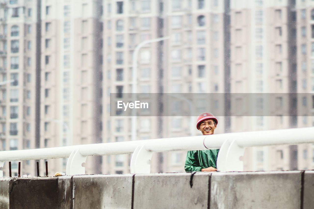 Portrait Of Happy Man Standing On Bridge Against Buildings